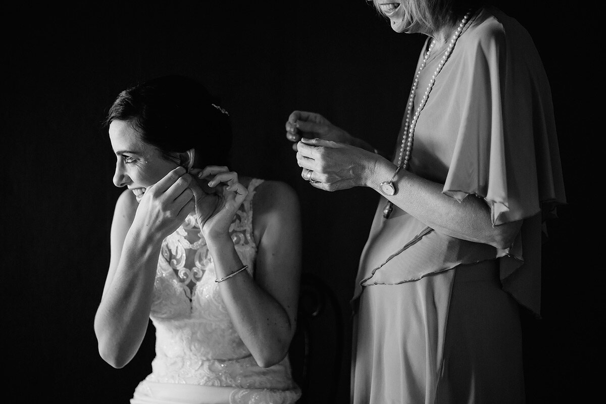 Bride putting on her earrings with her mother in the backround.