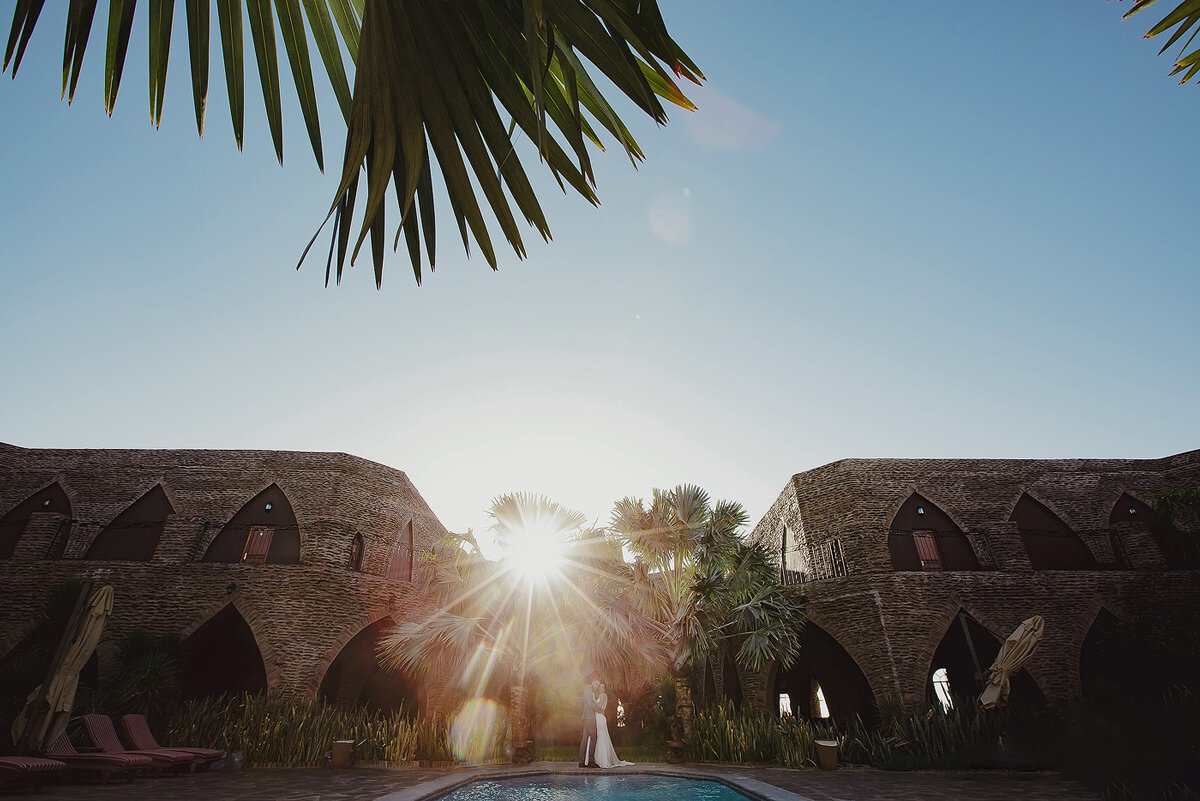Creative wedding couple portraits at a castle in the Namibian desert.