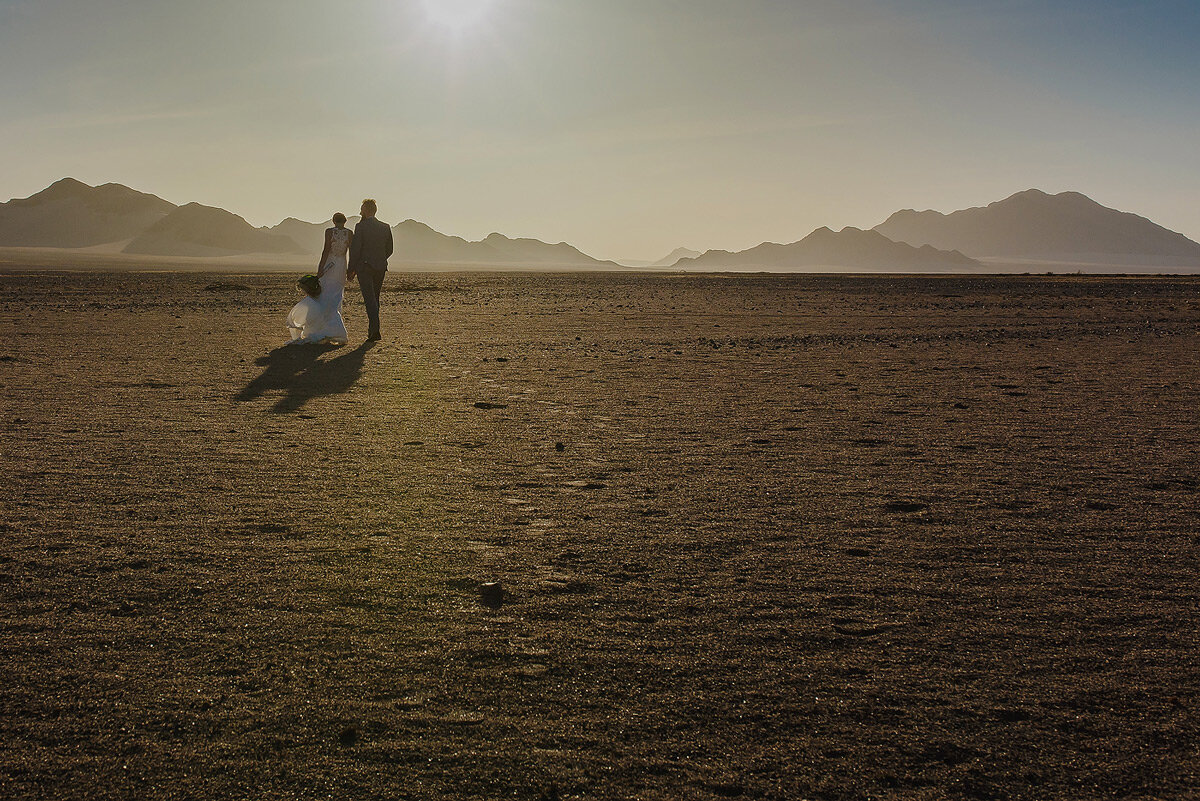 Sunset wedding couple portraits in Namibia with the Namib desert in the backround.
