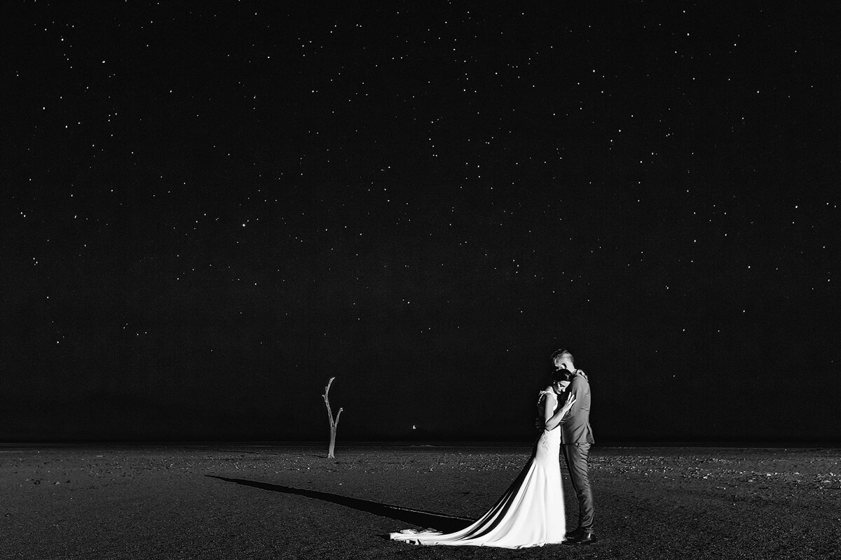 Night Time wedding couple portraits with the bride and groom and the full moon and stars in the Namibian Desert.