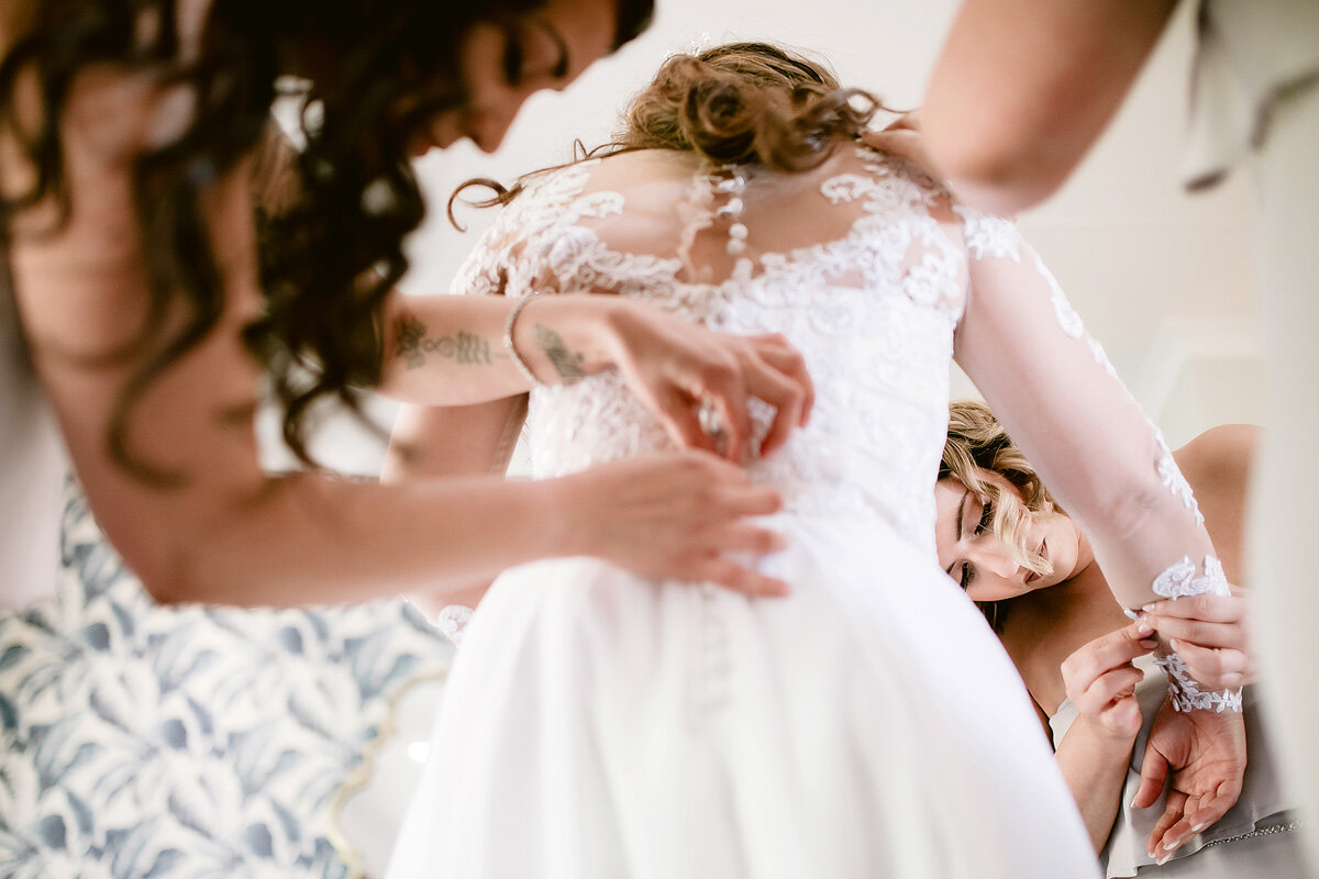 Bridesmaids helping the bride to put on her wedding gown in Northern Cape South Africa.