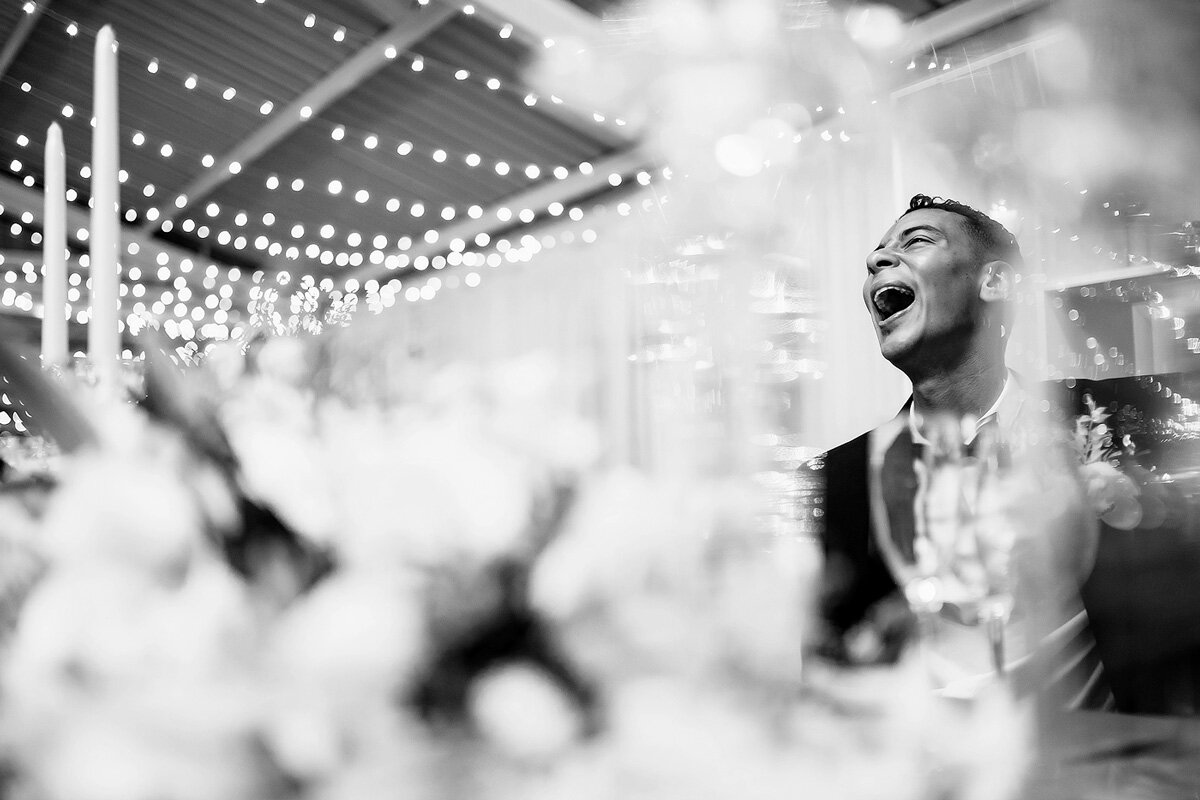 Groom reacts with laughter during the wedding toasts.