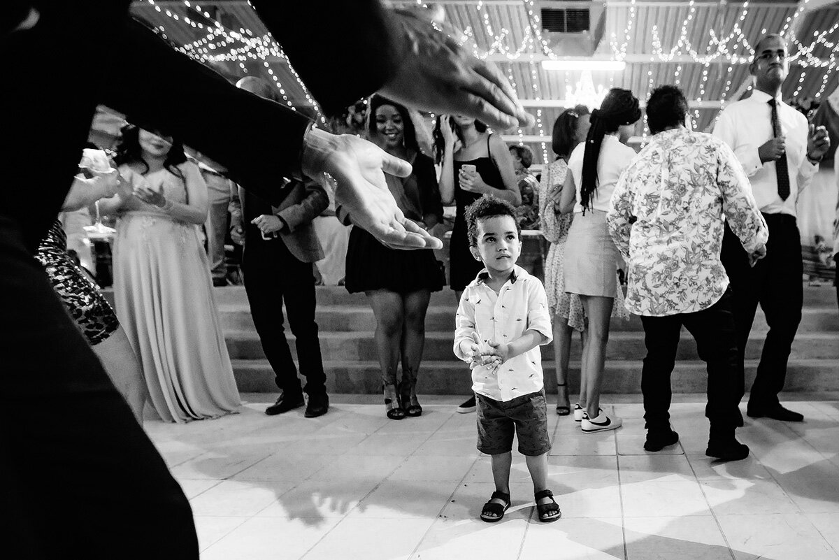 Kids at weddings on the dancefloor with father clapping in anticipation.