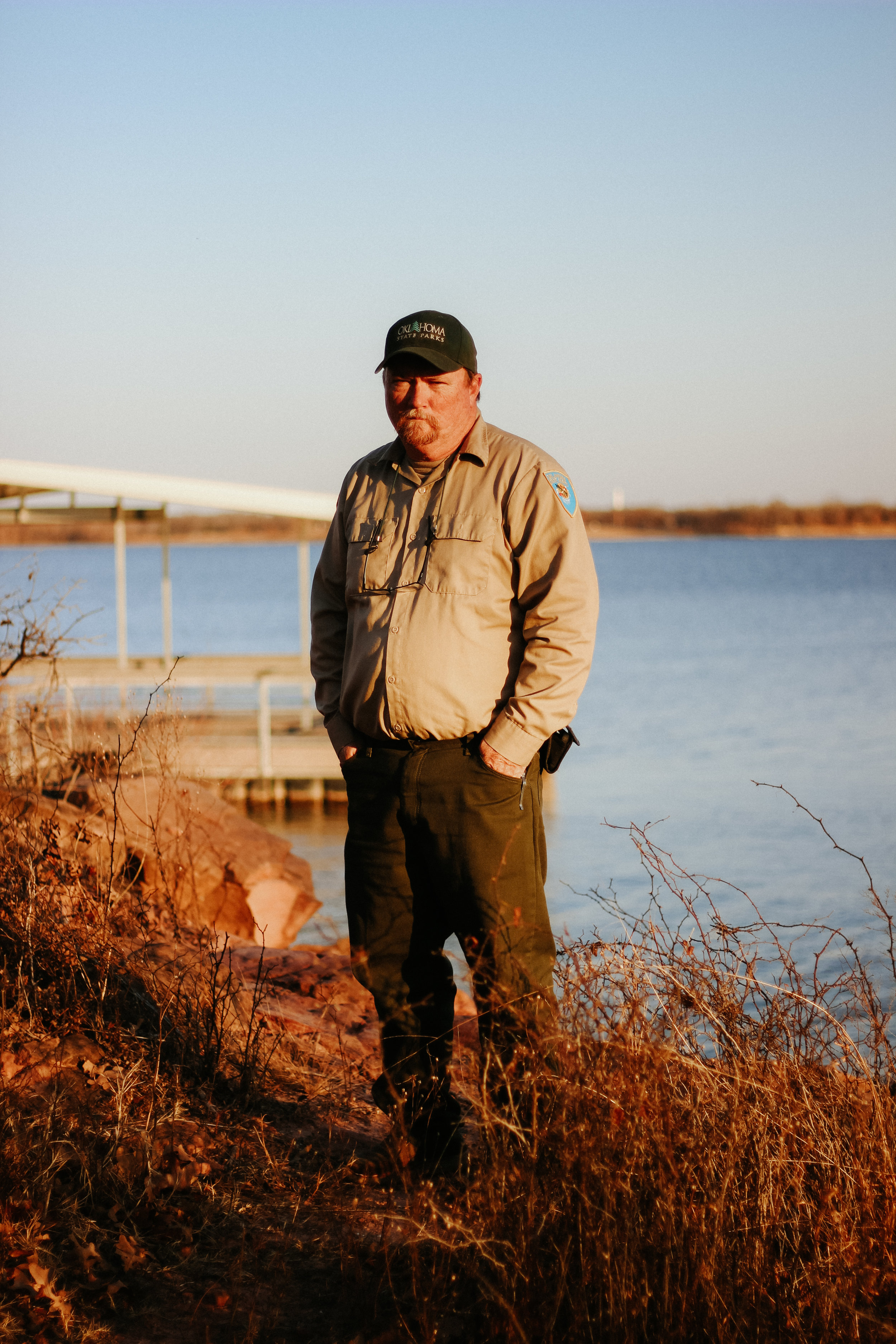 Sherman stands on the shore of Lake Thunderbird, the park's newest fishing dock behind him.