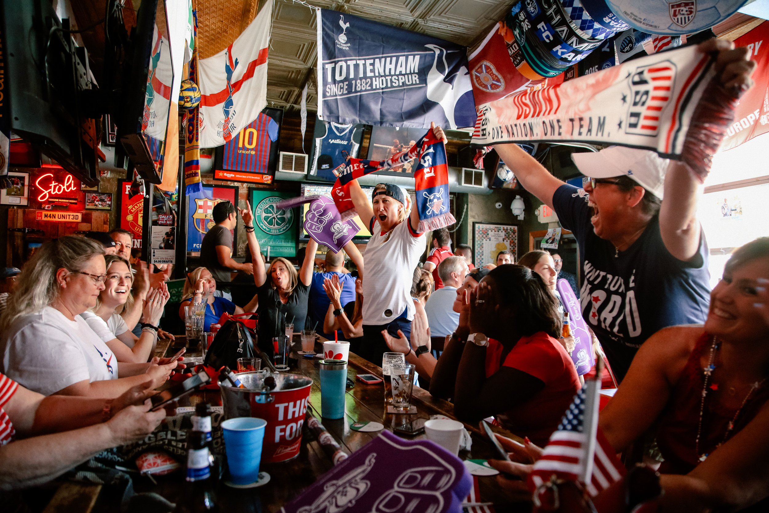 Angela Porter and Jill Boeckman raise their scarves over the cheering crowd at Empire Bar after the United States women's national soccer team beat France 2-1 in the Women's World Cup quarterfinal game on June 28, 2019.