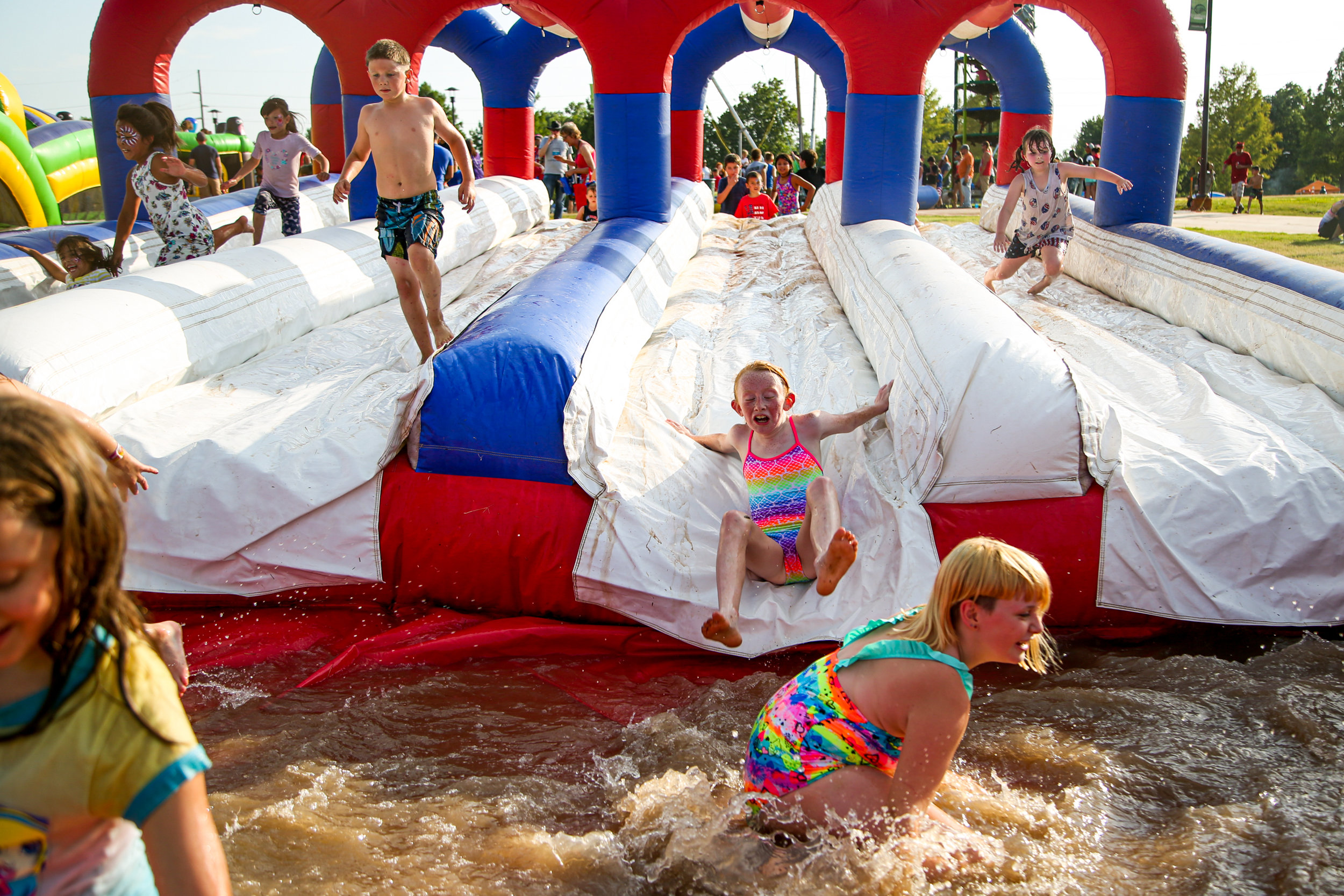 Children play on an inflatable waterslide during FreedomFest at River West Festival Park in Tulsa on July 4, 2019.