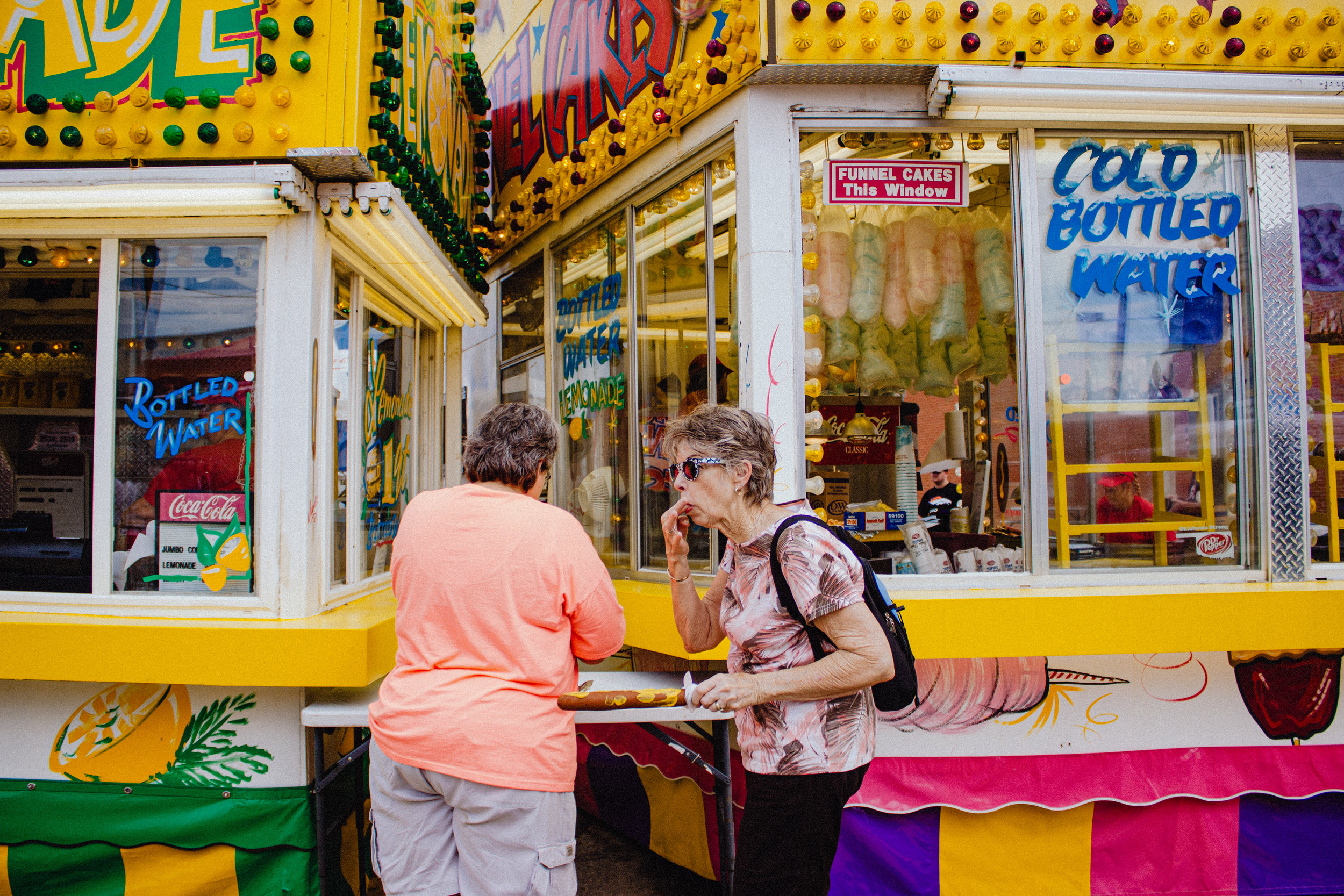 A pair of fairgoers add toppings to their corndogs on the opening day of the Oklahoma State Fair in Oklahoma City on September 14, 2016.