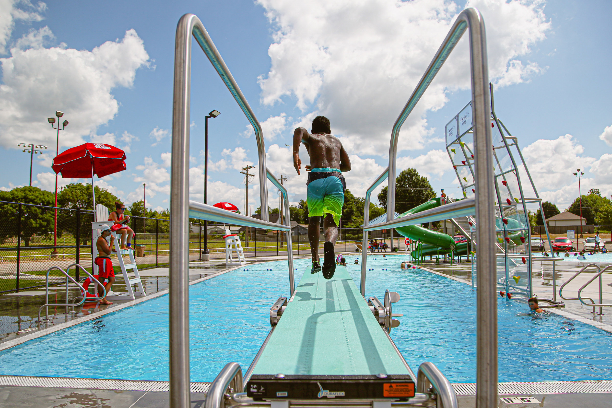 Raion Hill runs off the diving board into the newly-opened pool at Lacy Park in Tulsa on July 12, 2019.