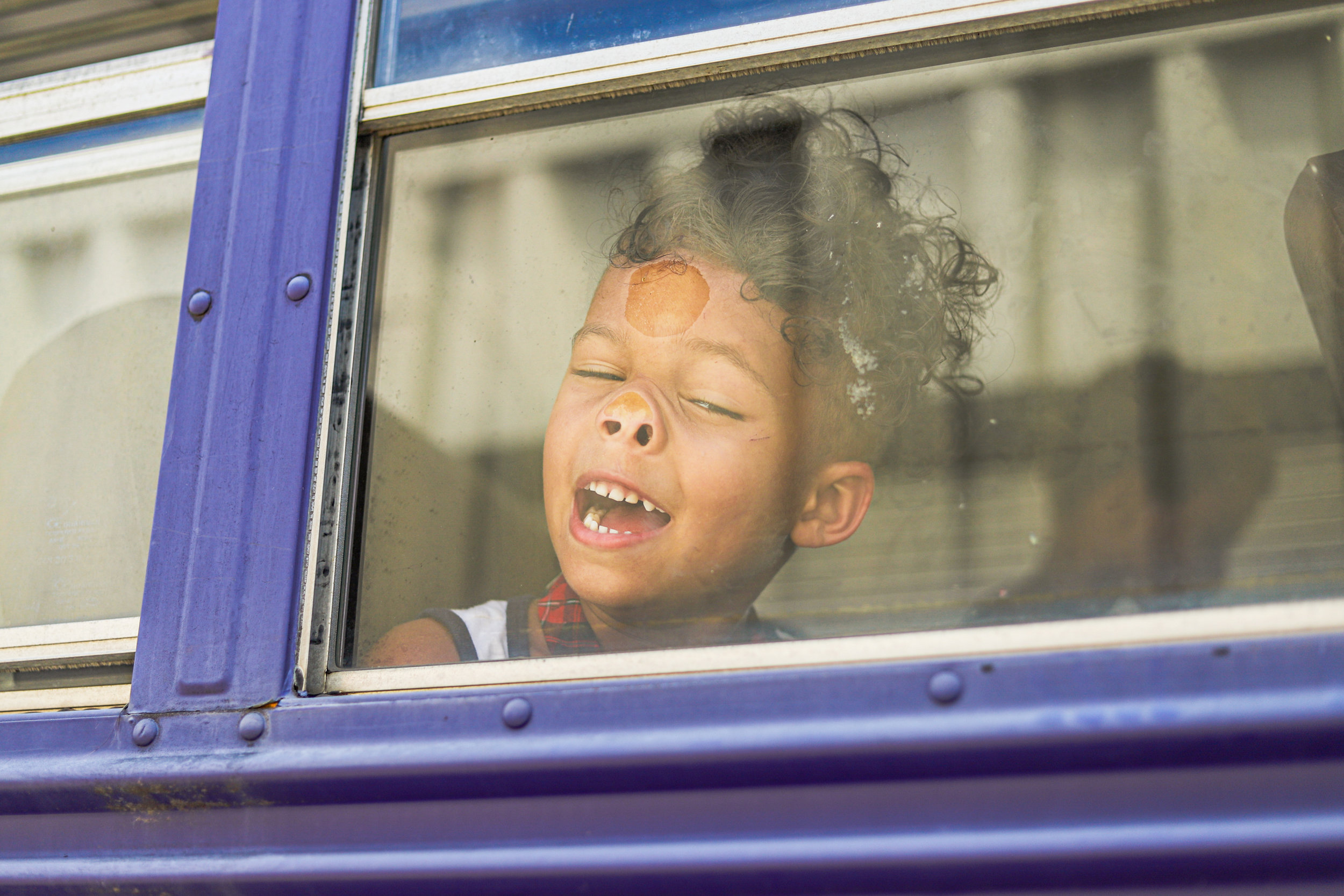 A child presses his face against the glass window of the bus headed to lunch during the YouthWorks Summer Leadership Camp, a summer learning program for at-risk kids, held at Wesley Chapel in Tulsa, Oklahoma on July 8, 2019.