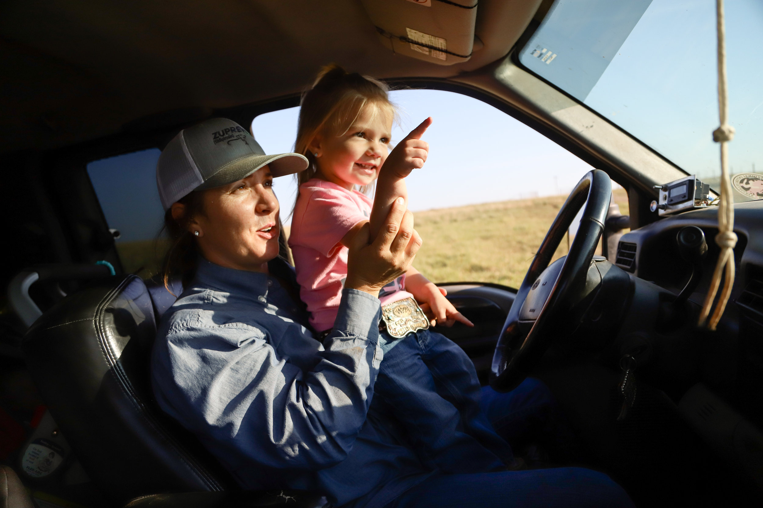 Jenna Stierwalt holds her 2-year-old daughter, Sonora, as she points out her uncle riding by on a tractor at Stierwalt Ranch in Burbank on July 27, 2019.