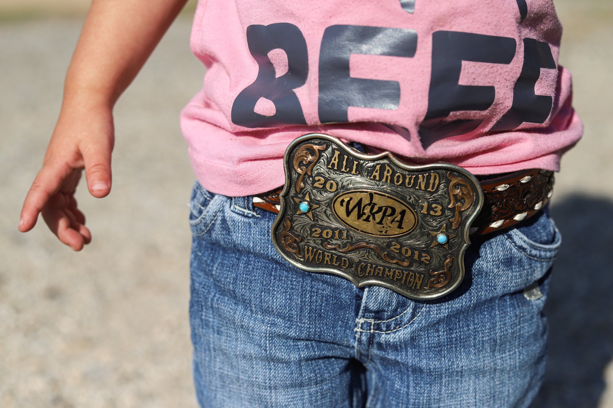2-year-old Sonora Stierwalt proudly wears one of her mother's rodeo buckles at Stierwalt Ranch in Burbank, Oklahoma.