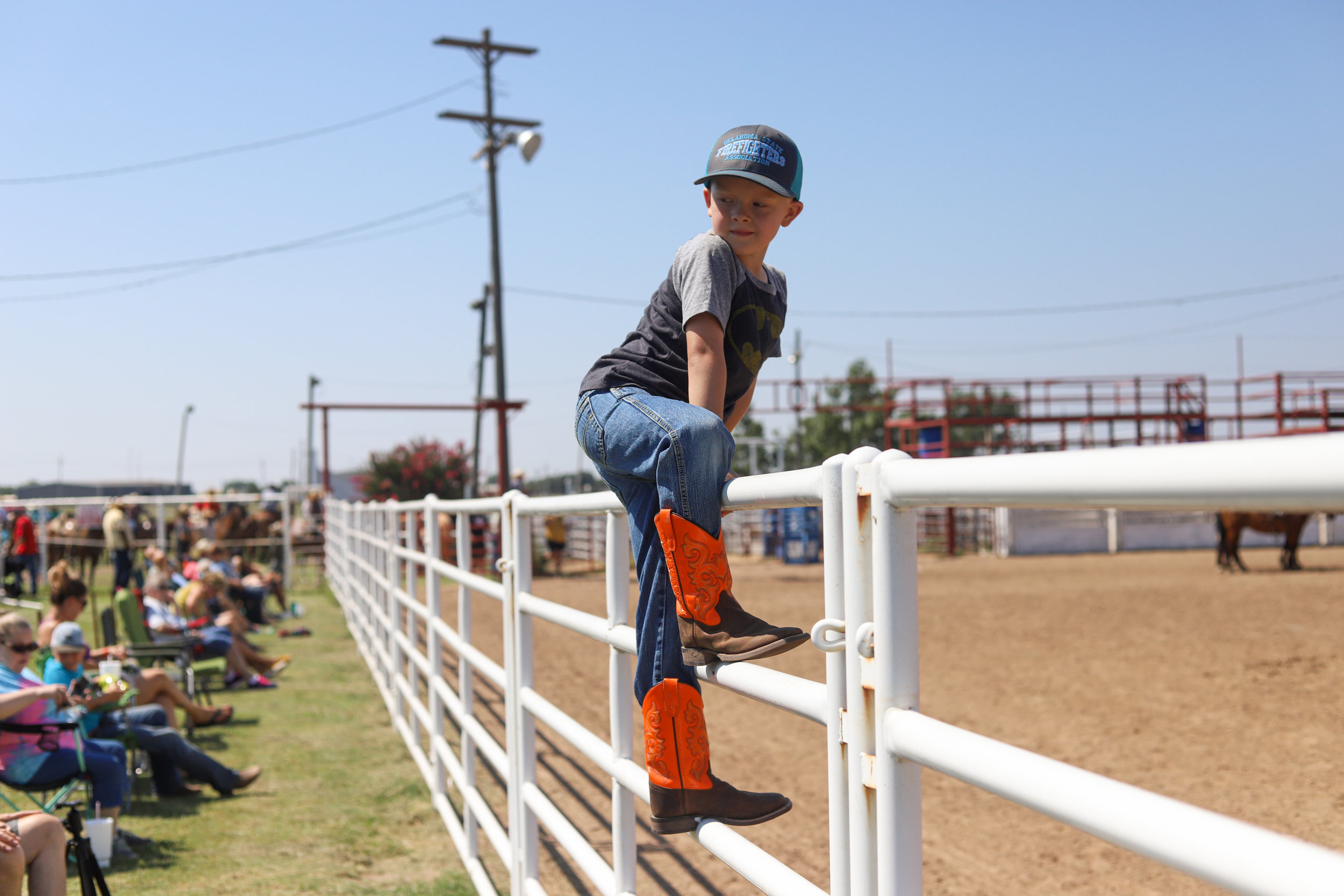 A young boy climbs on a fence to watch a cattle roping event during the youth ranch rodeo at the 101 Arena in Ponca City, Oklahoma.