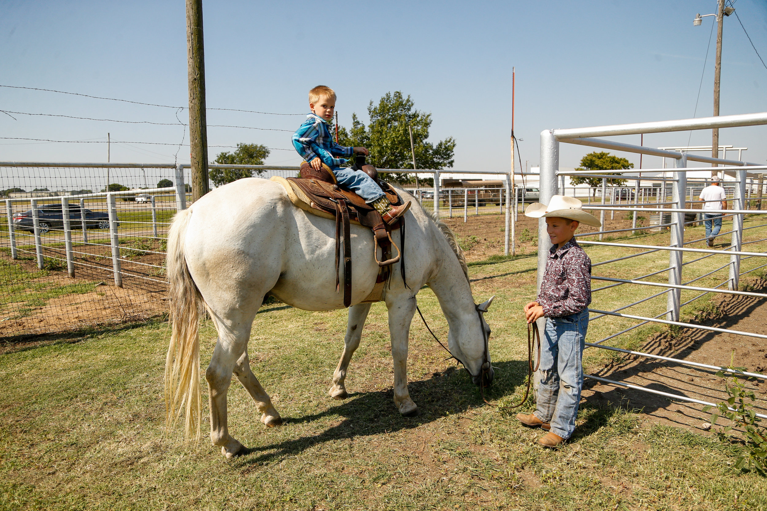 A pair of young boys walk their horse around the pens at a youth ranch rodeo at the 101 Arena in Ponca City on July 27, 2019.
