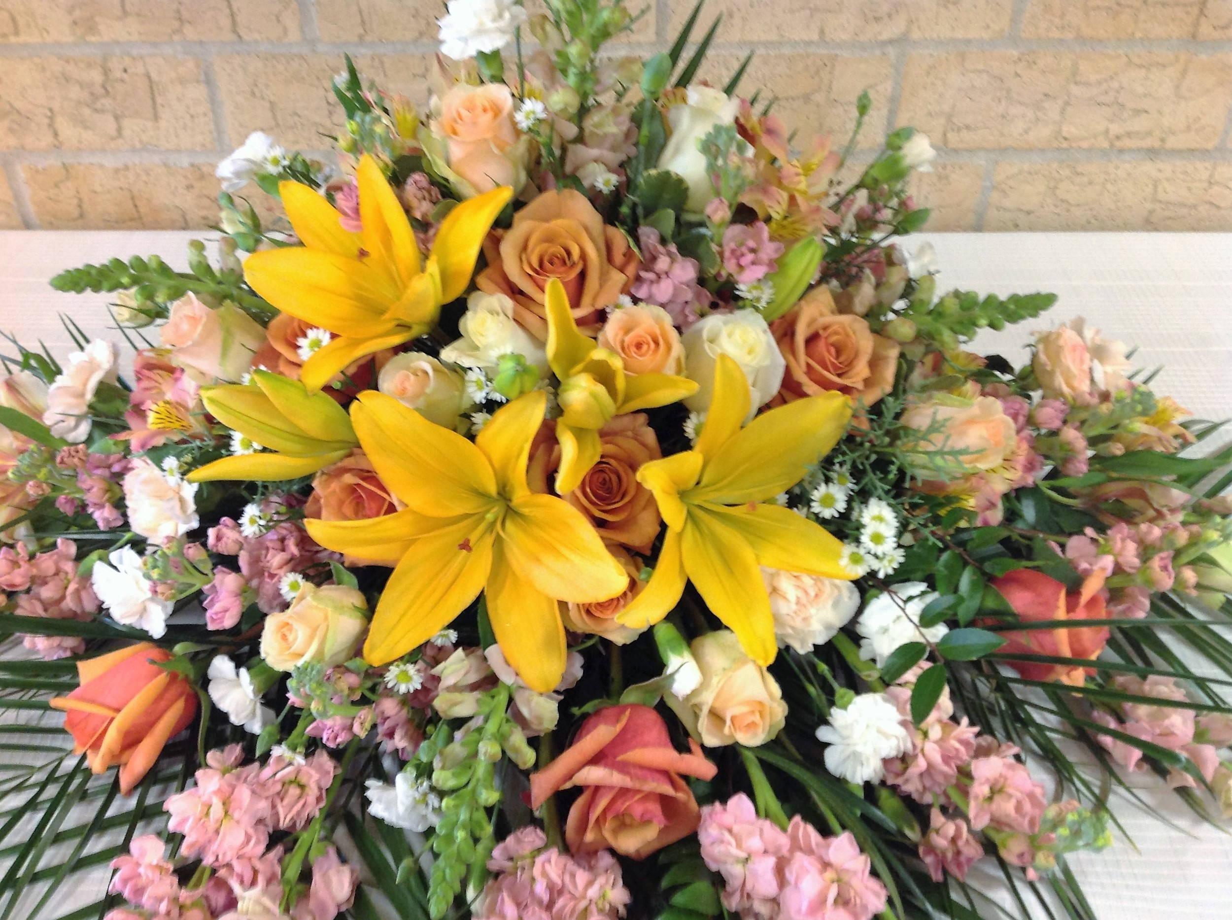 #2 Yellow lily, peach roses, multi colored casket spray