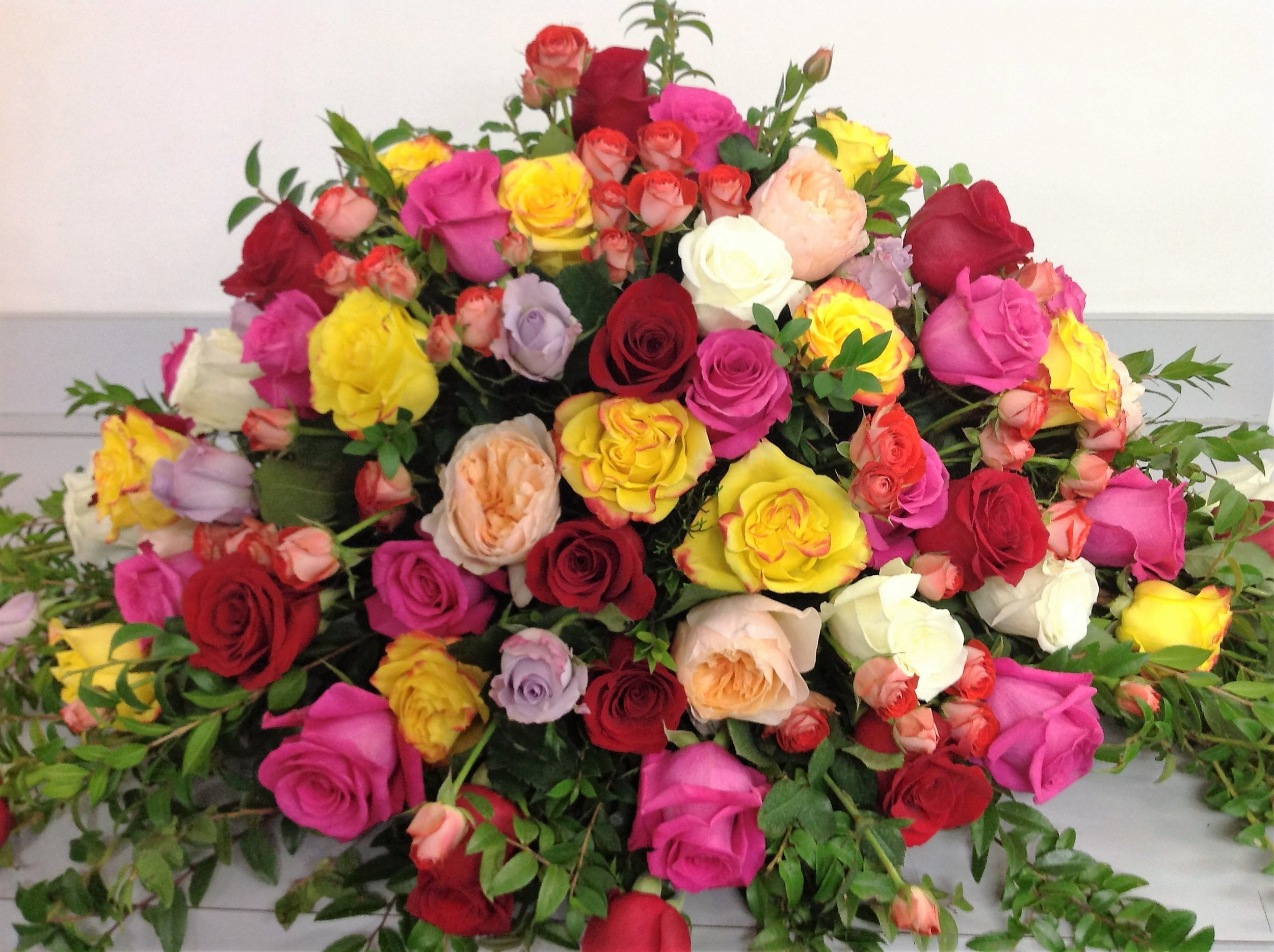 #7 Roses of all colors rounded formal casket spray
