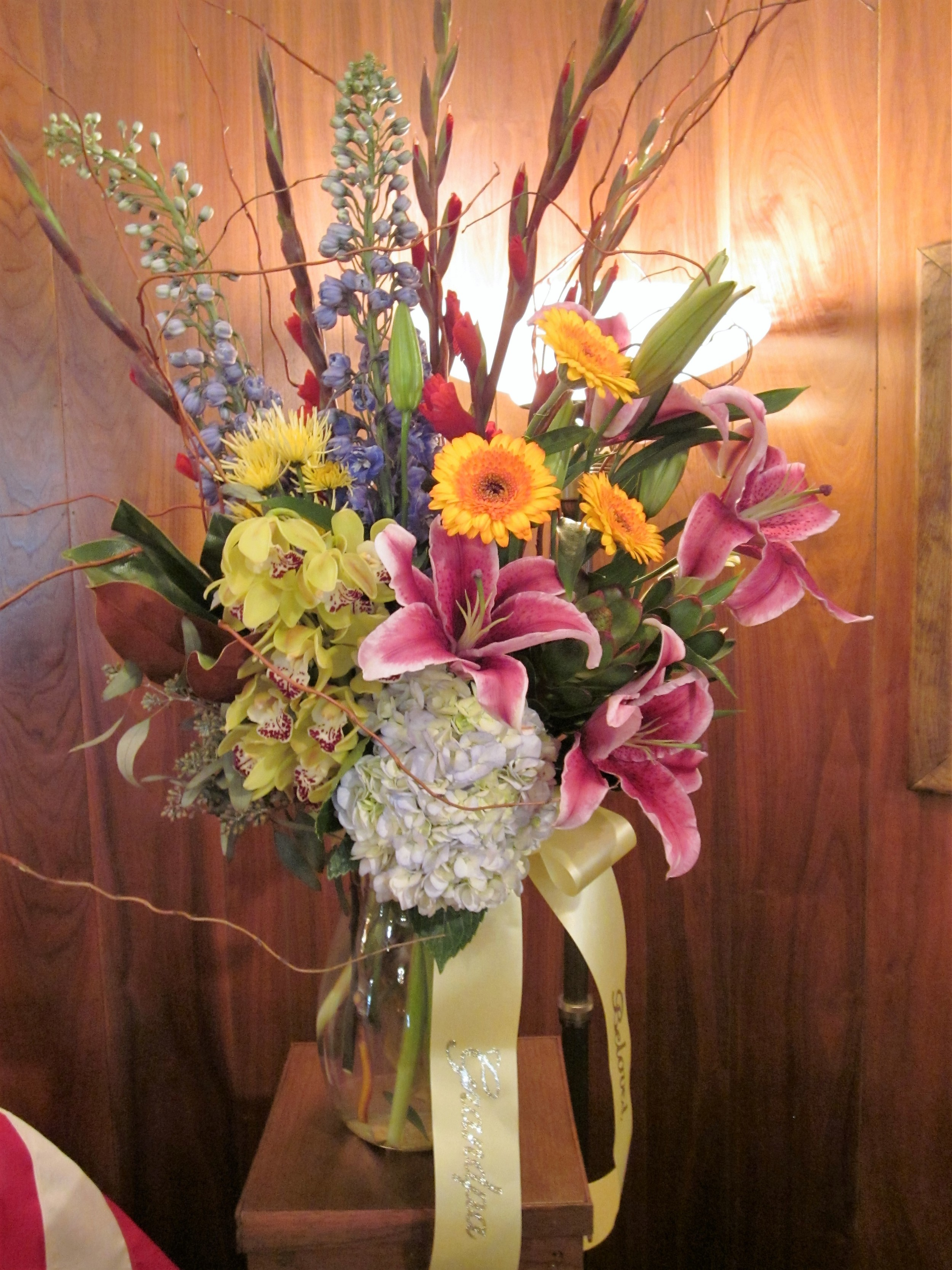 #18 Bright colored vase arrangement of lily, gerbs and orchid.