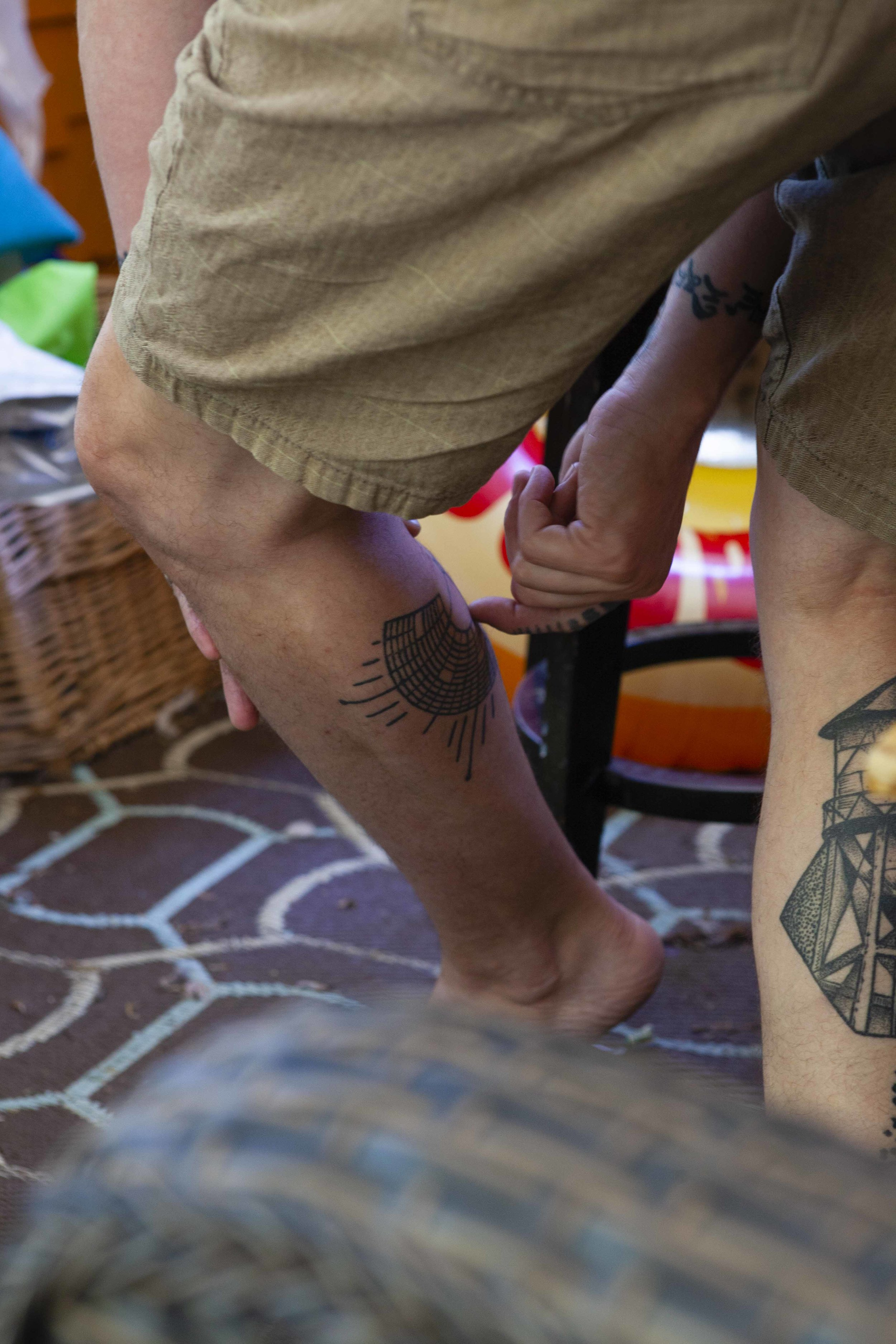 Eric points something out on the Burning Man map tattooed on his leg. He likes to point.