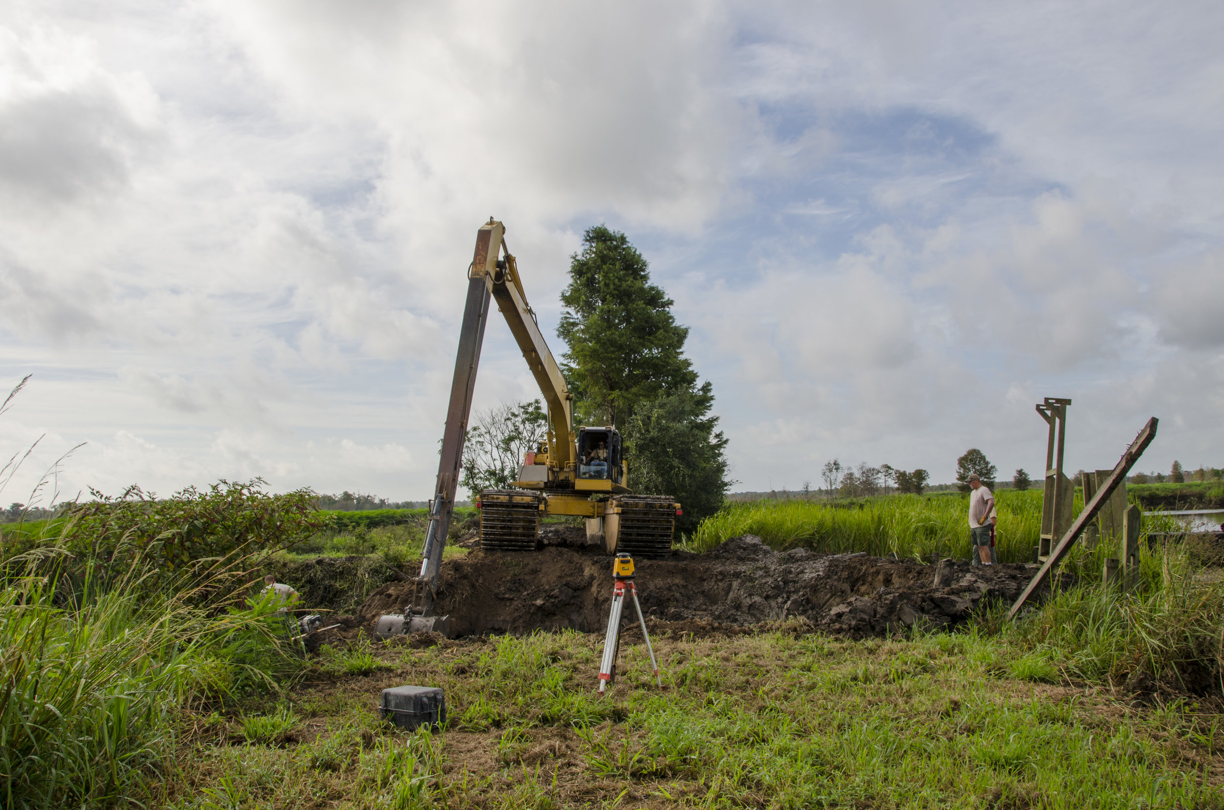 Electronic levels and surveying tools help the crew make an accurate dig.