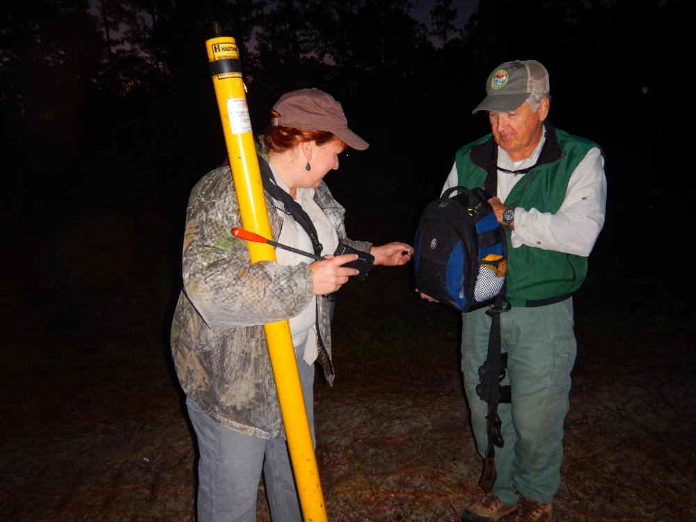 """SCDNR RCW Project Leader Caroline Causey and Regional Biologist Dean Harrigal demonstrate some of the equipment used by the biologists who study the birds. """"Peeper cams"""" on extendable poles allow them to look into a nest cavity to check on the birds, and the resulting images or video can be captured and transmitted to a laptop computer on the ground."""