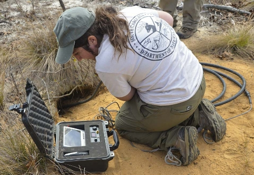 "(Above) Jonathan Cooley & Joel Mota  use a VHF receiver to get a fix on a transmitter-tagged tortoise in its burrow. (Below) Olivia Thomas uses a ""scope"" -- a tiny camera attached to a flexible fiber-optic cable -- to get a visual a a tortoise in its burrow."