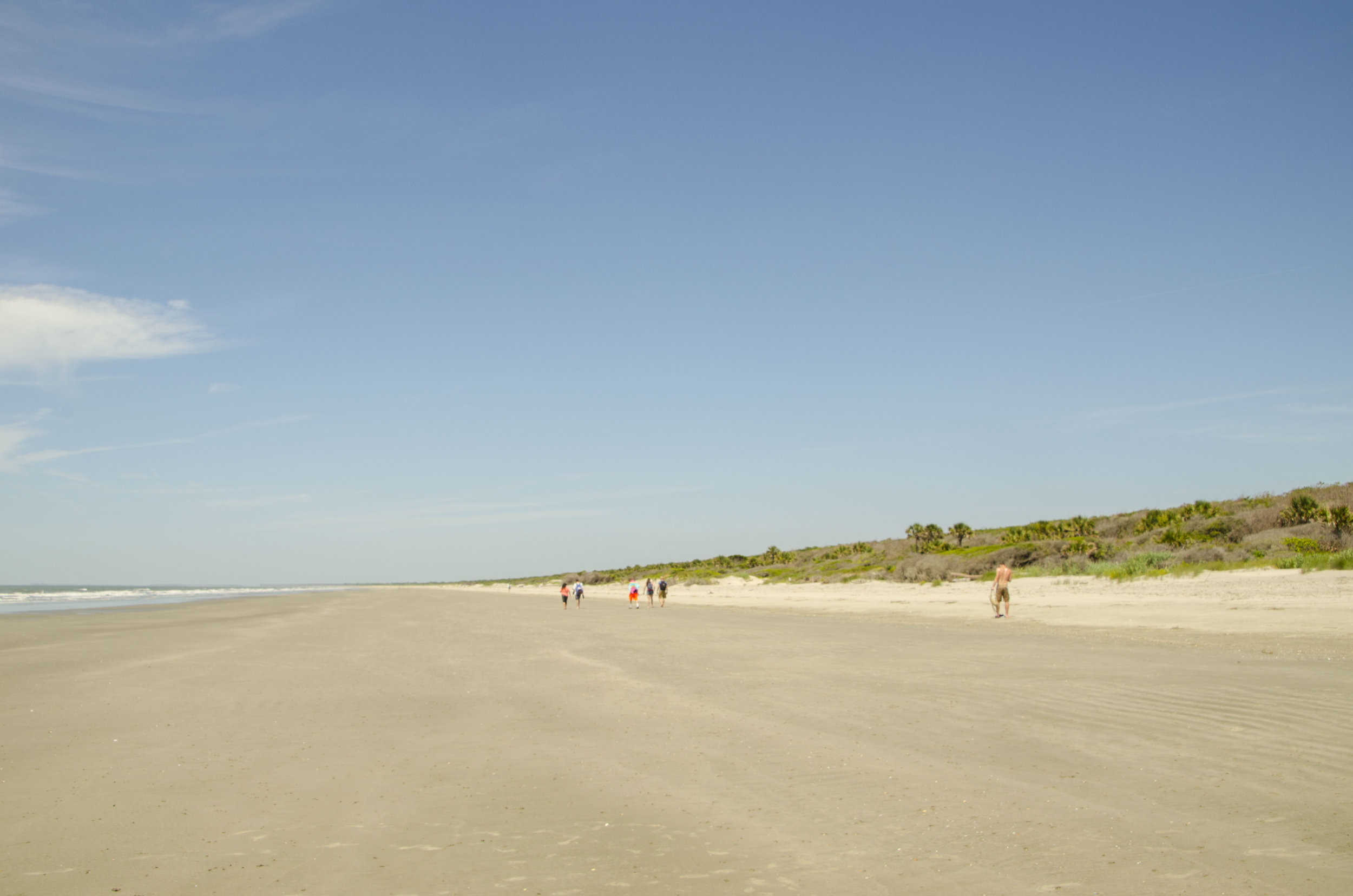 These folks are headed south on the beach, the best area to fund shells.