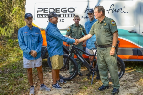 Coker Day (left) shakes hands with SCDNR's Major Gary Sullivan after delivering the Pedego bike.