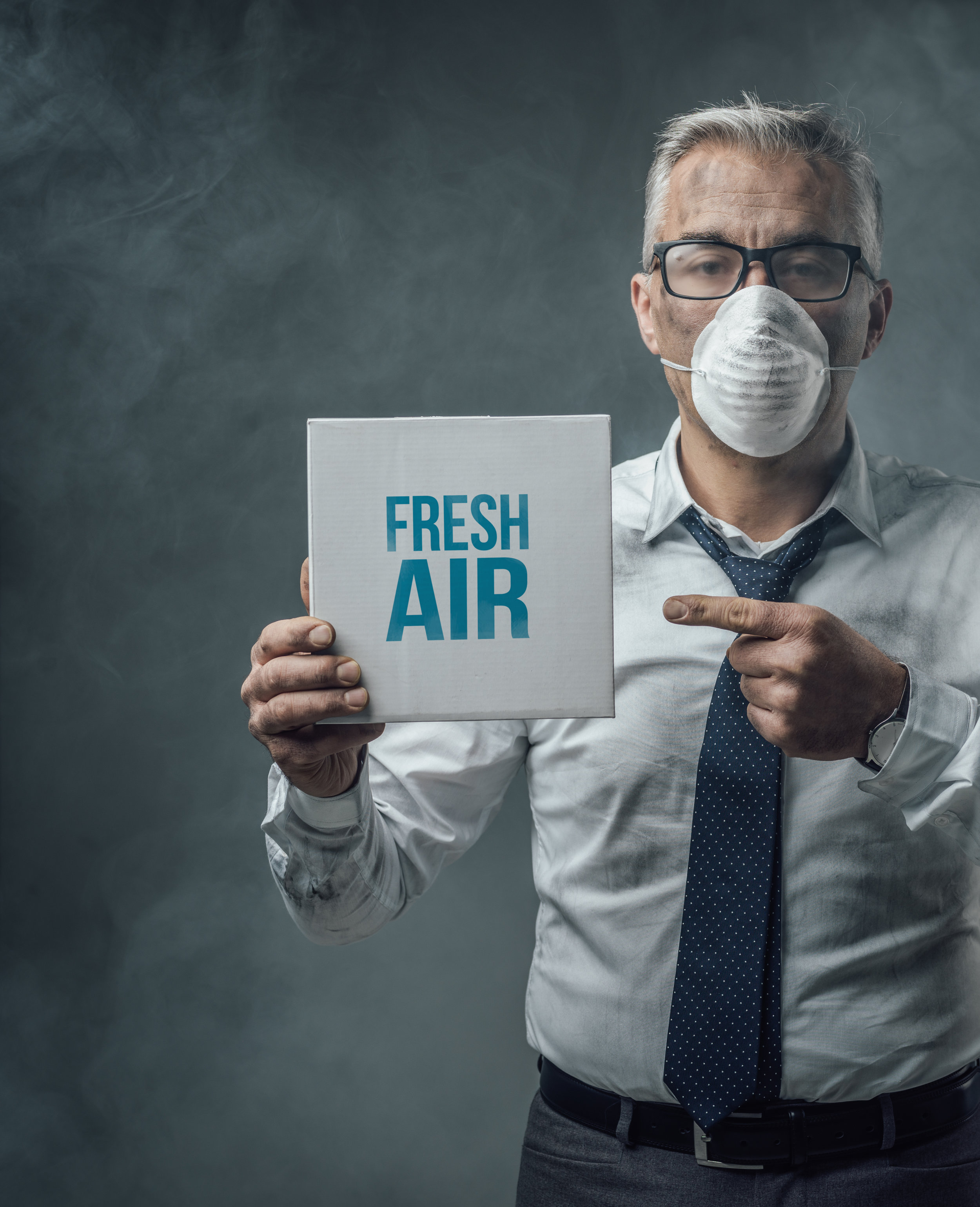 businessman-holding-a-sign-and-air-pollution-PCD58LL.jpg