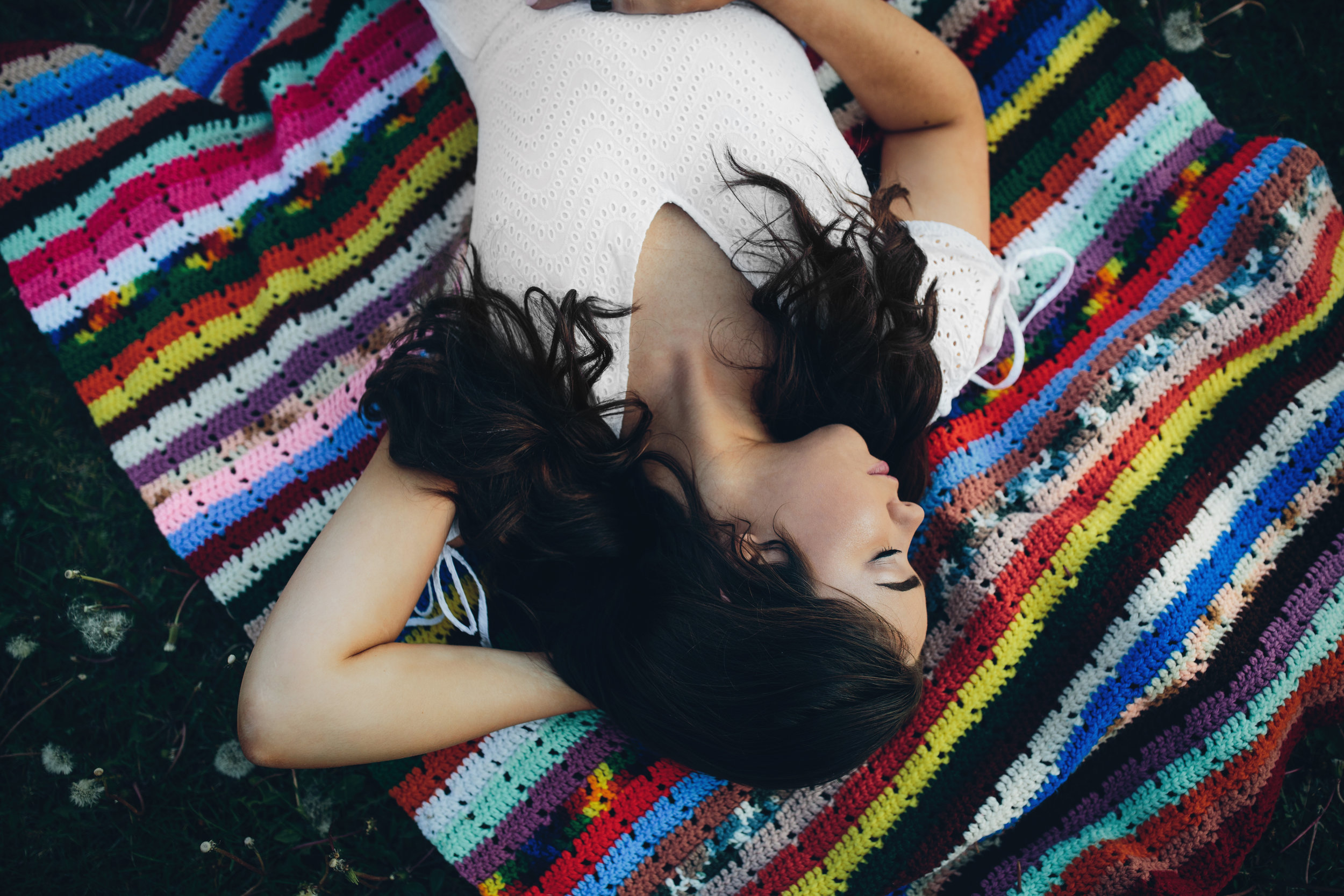 Senior picture laying on a vintage blanket by Jolene Dombrowski