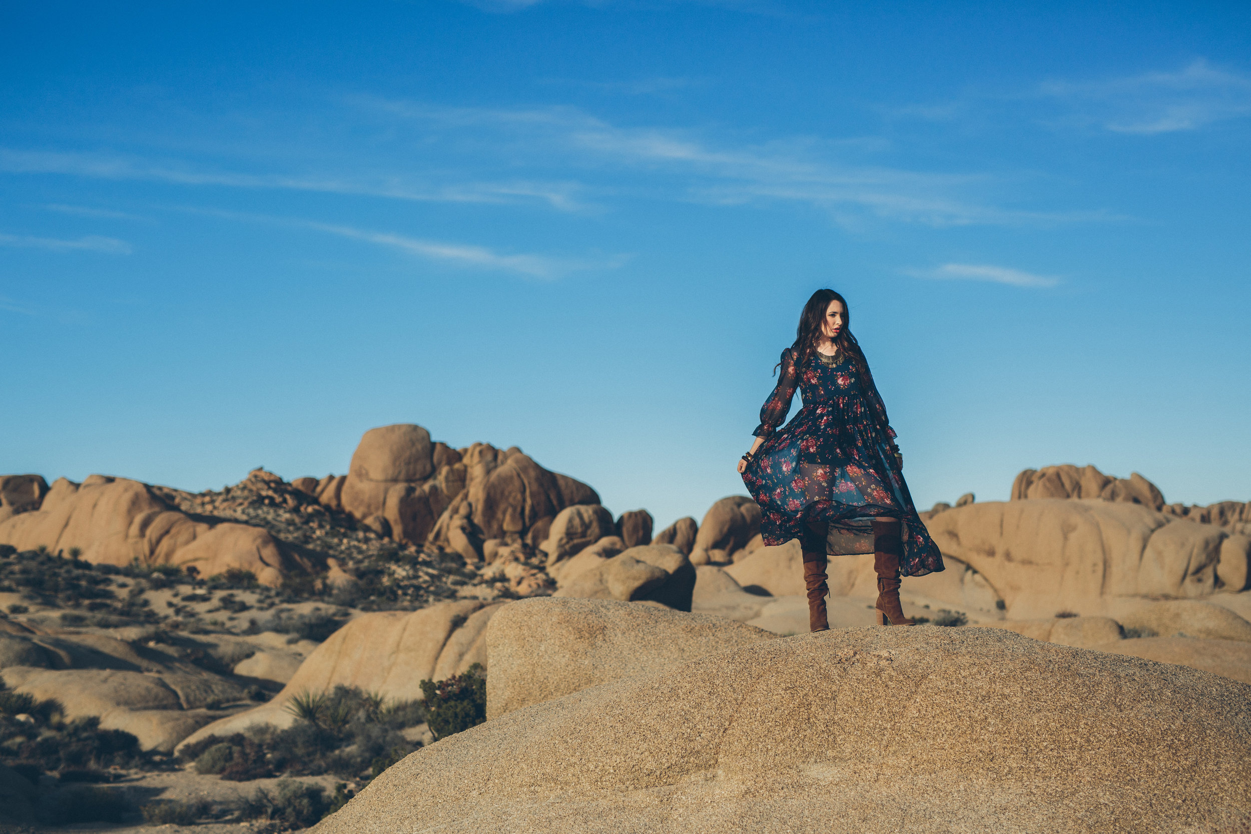 Senior photo on rocks in Joshua Tree National Park of girl in long dress with knee high boots. Photo by Jolene Dombrowski