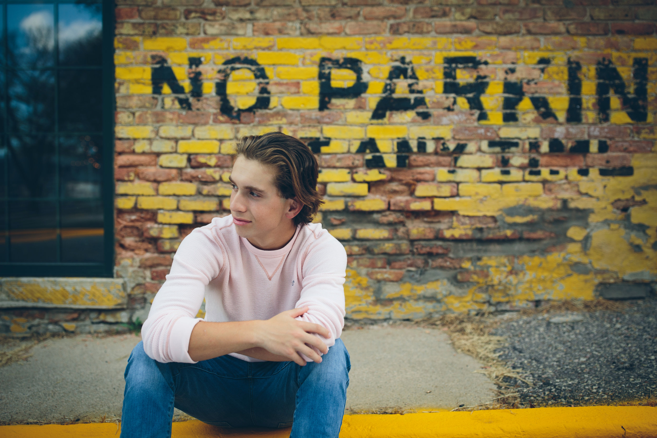 Boy senior photo in front of brick no parking sign. Baraboo, WI.