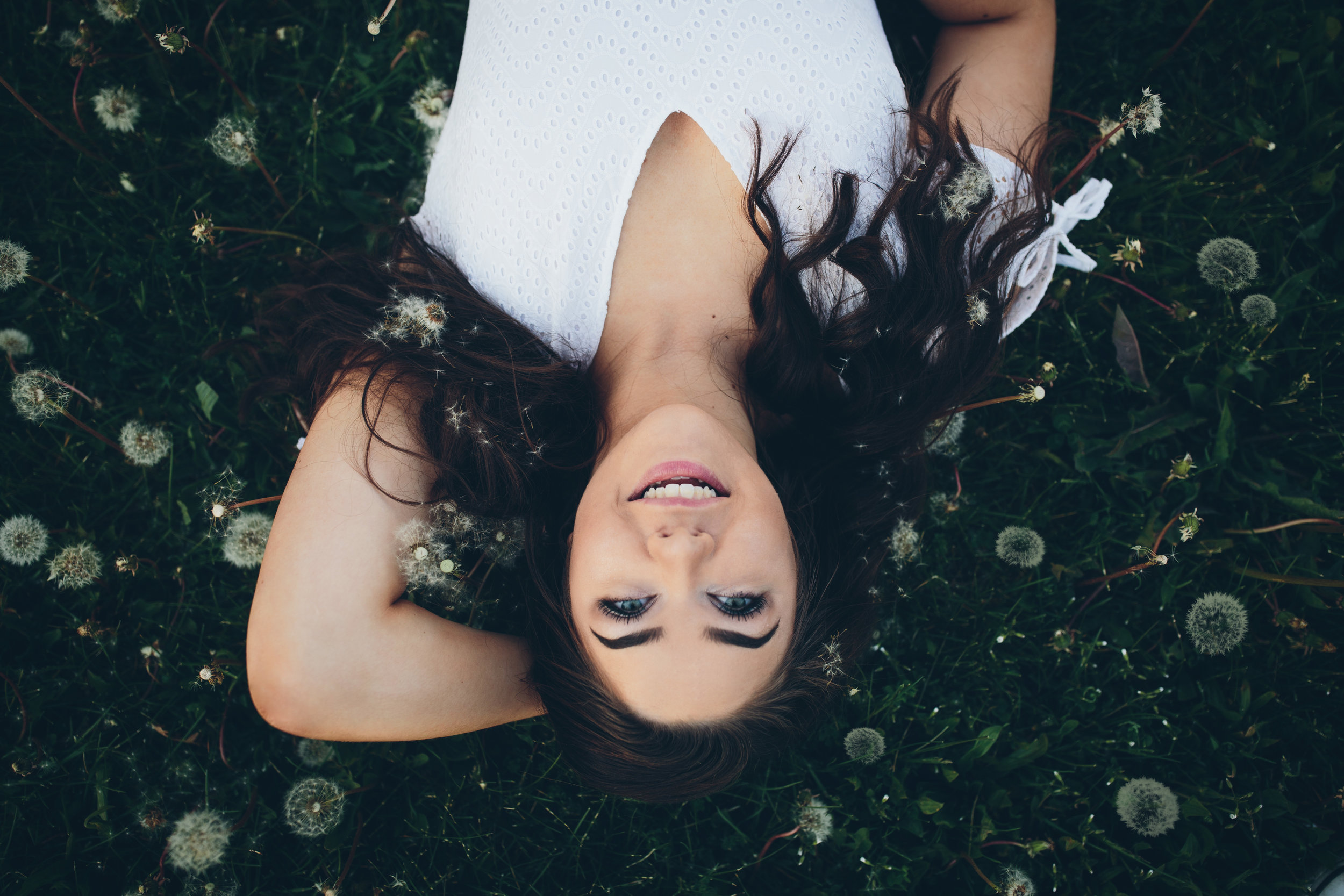 Girl laying in dandelions. Senior picture taken in madison, WI.