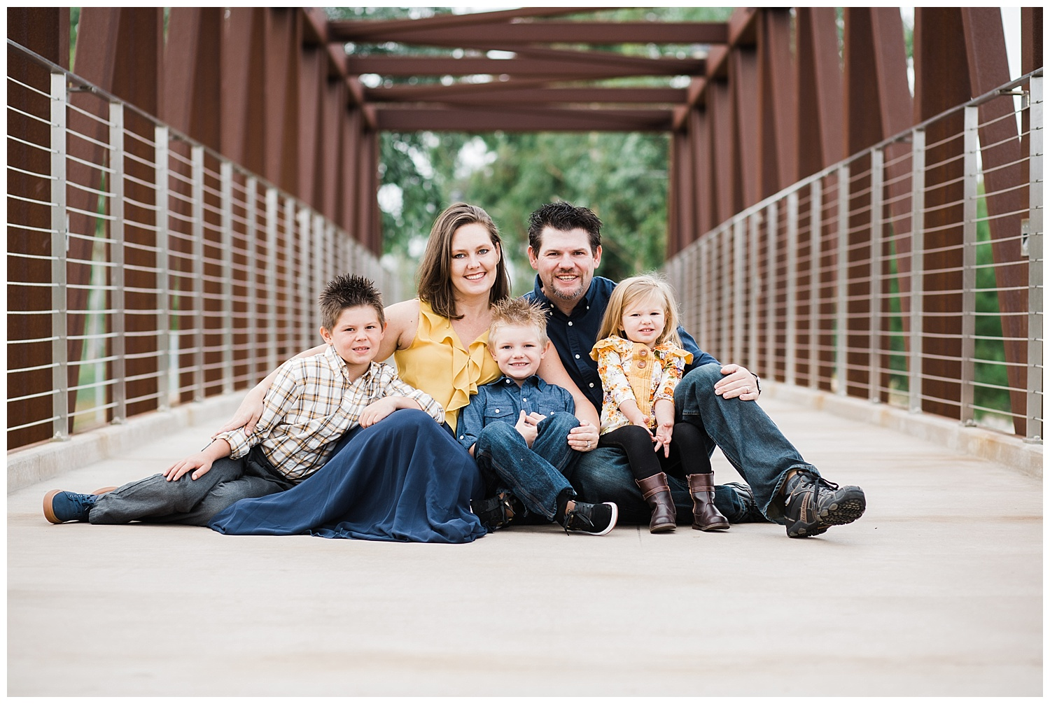 Kari Webb Photography | Orange County Photographer | Family wearing navy and mustard sitting on bridge