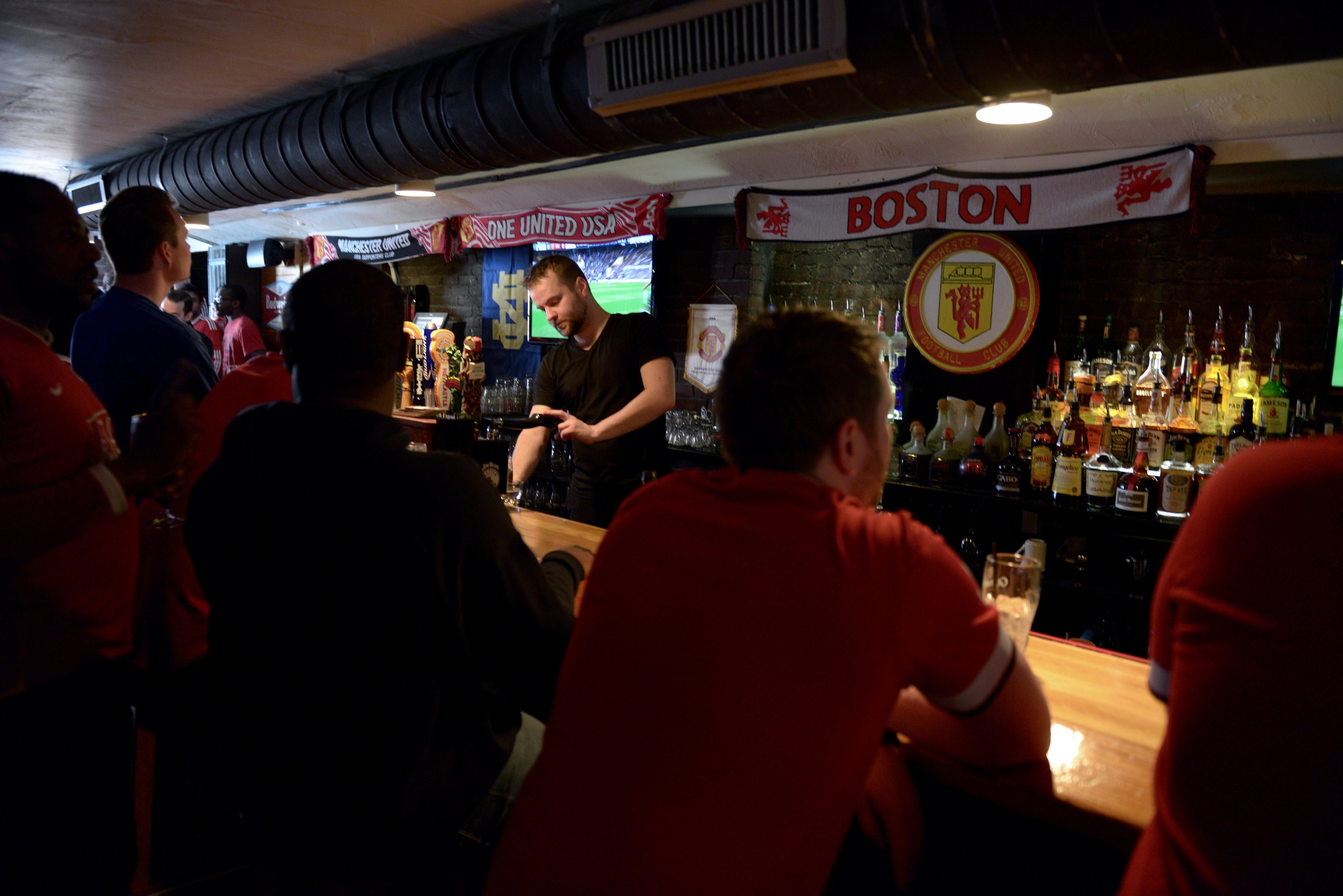 Televisions line both sides of the room. Some sit at the bar, while others gather in pockets around the screens.