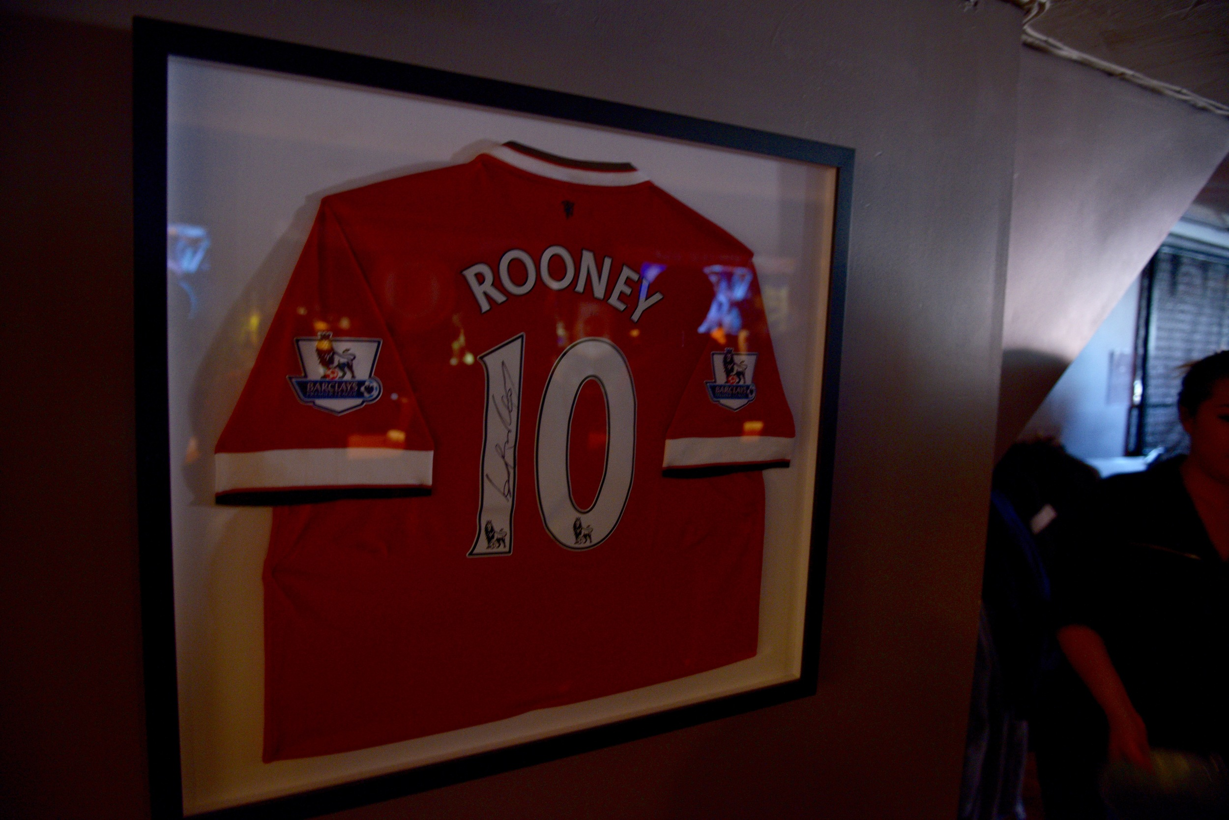 A signed Wayne Rooney jersey hangs on the wall of Crossroads Irish Pub. Rooney has played for the club for 12 years, scored over 260 goals, and won 12 trophies with the club