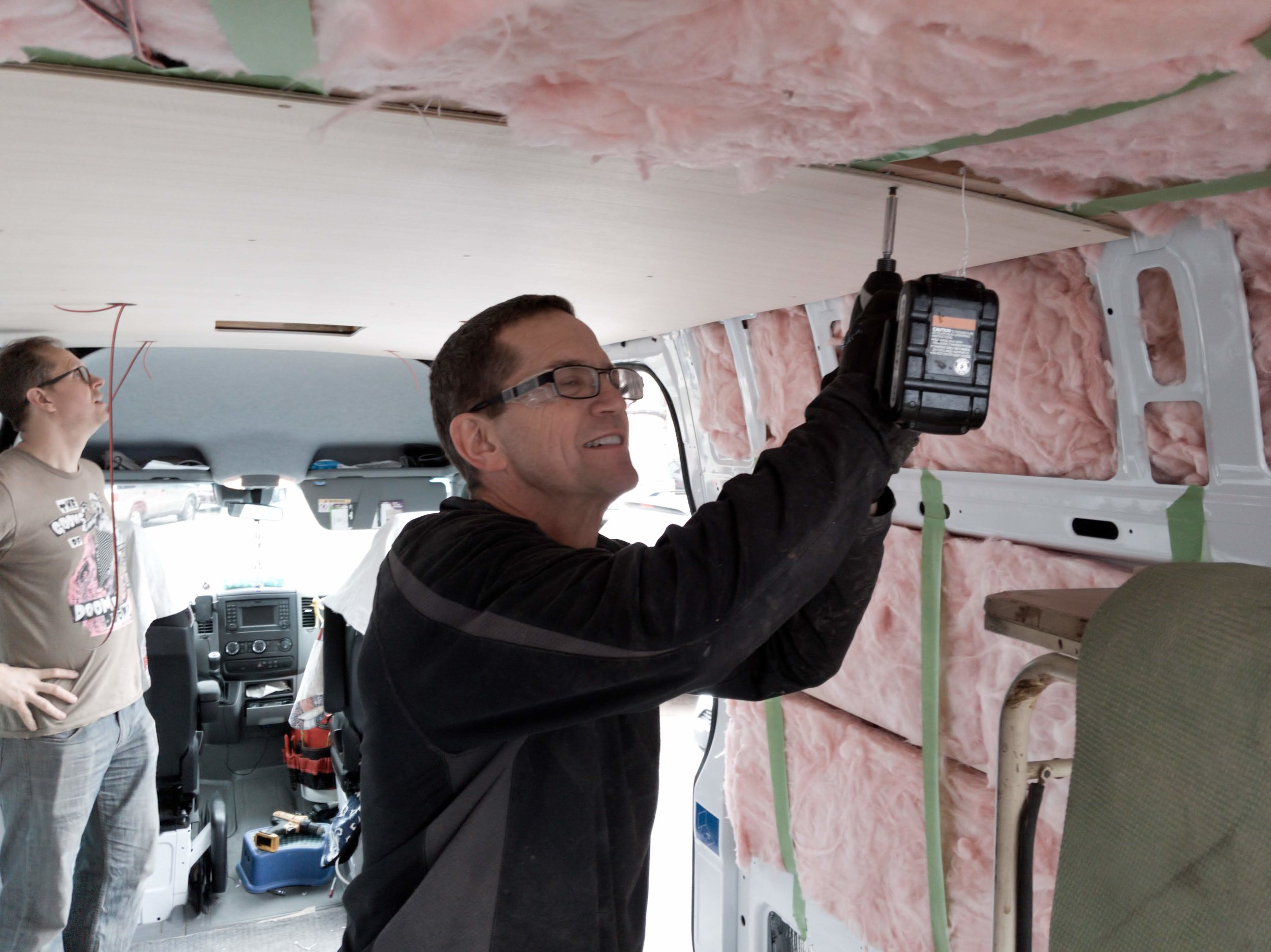 Screwing the ceiling panels in place