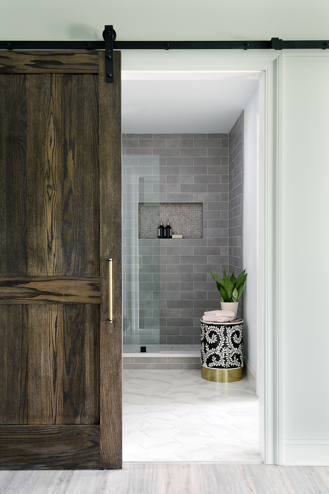 The sliding barn door adds the perfect final touch for this easy to access, modern bathroom. And check out that inlay stool that adds a pretty pattern to the space.