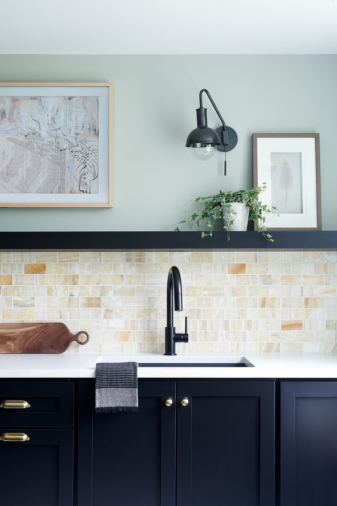 These shaker-style cabinets are a chic statement and conceal a trash & recycling bin and an integrated dishwasher for easy cleanup after the party. Onyx backsplash tile provides a warm, unexpected bright bit of color and the floating shelf is the perfect spot for glasses and art display.