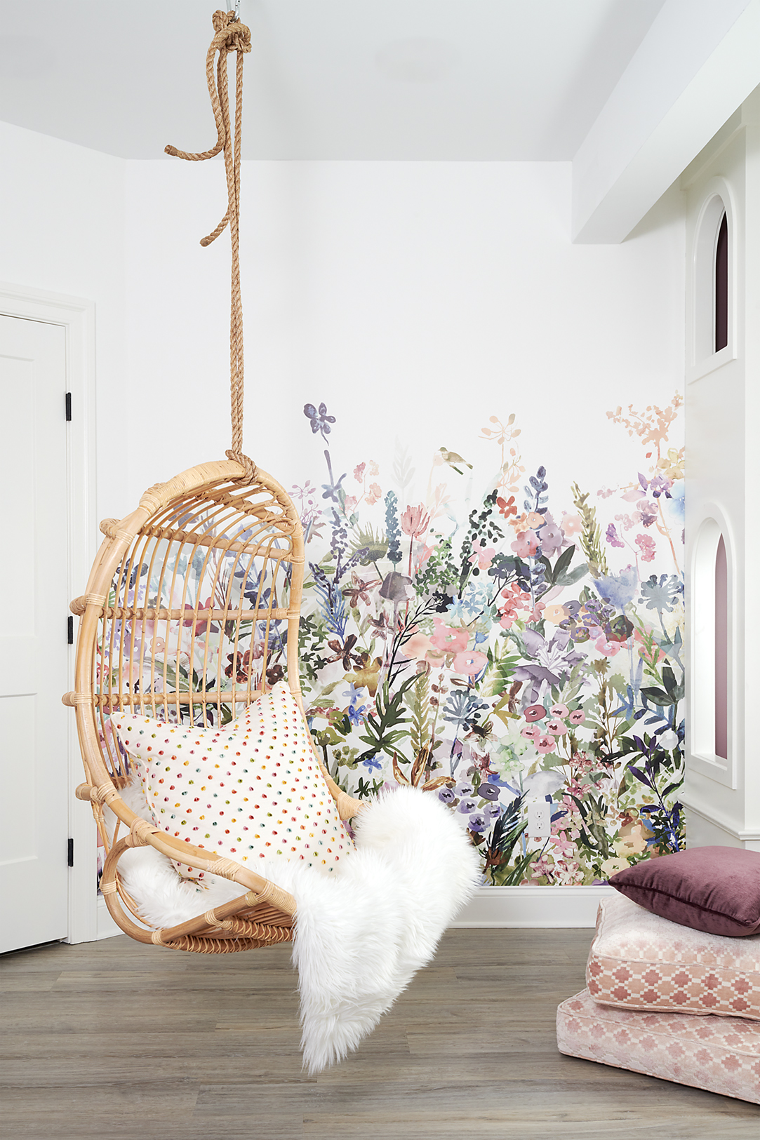 The floral mural on the left wall adds brightness to the space and includes all of the fun colors these girls love to tie together the room. Big, comfy floor pillows are great for adding softness for lounging. The luxury vinyl plank flooring also extends into this space for easy cleanup from art projects.