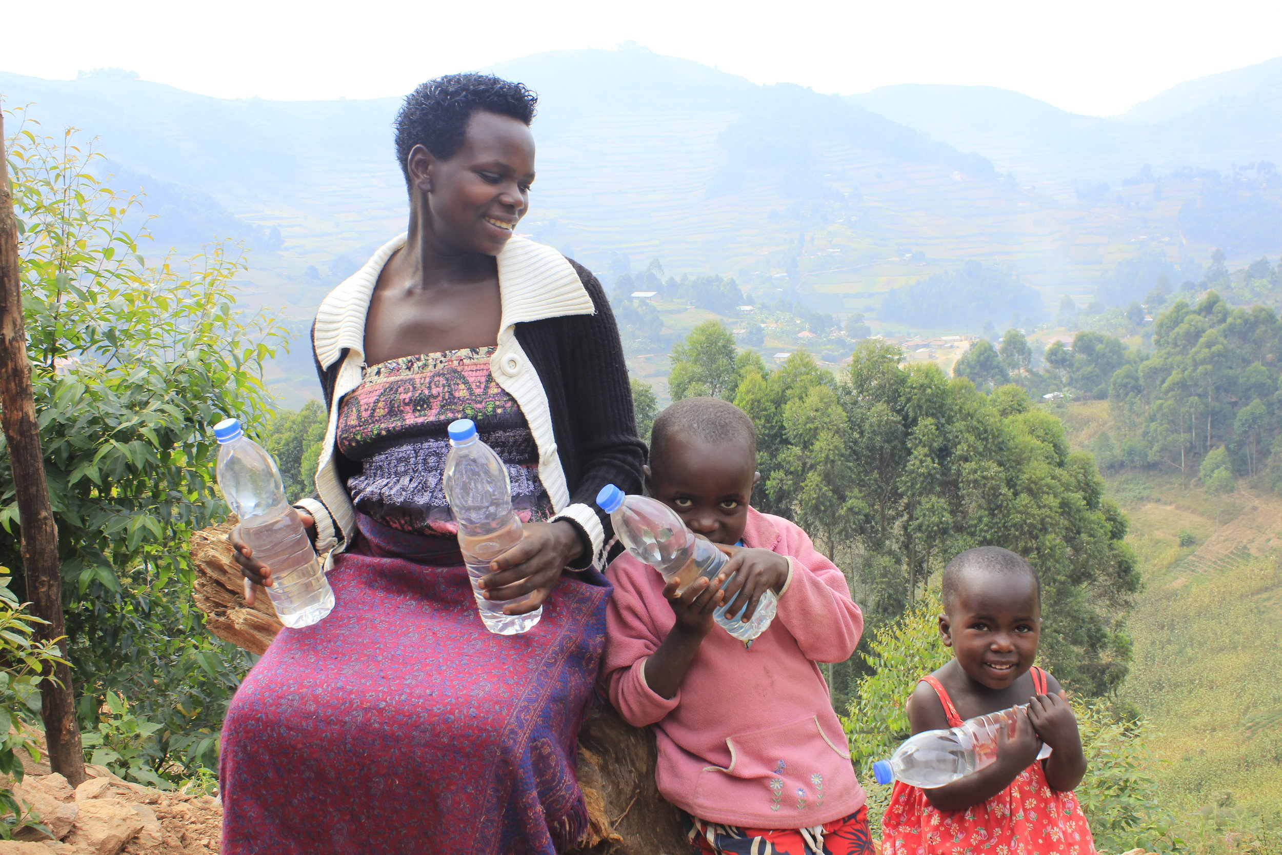 Mom and her two little ones drink clean water