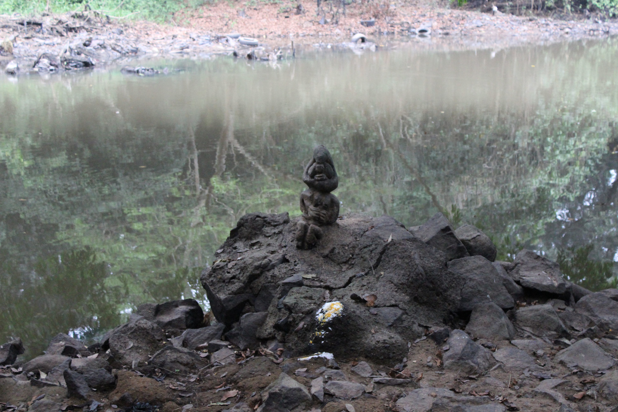 Oshun's Eshu with some offerings sitting next to the central statue at the Oshun river, dry season, 2015.