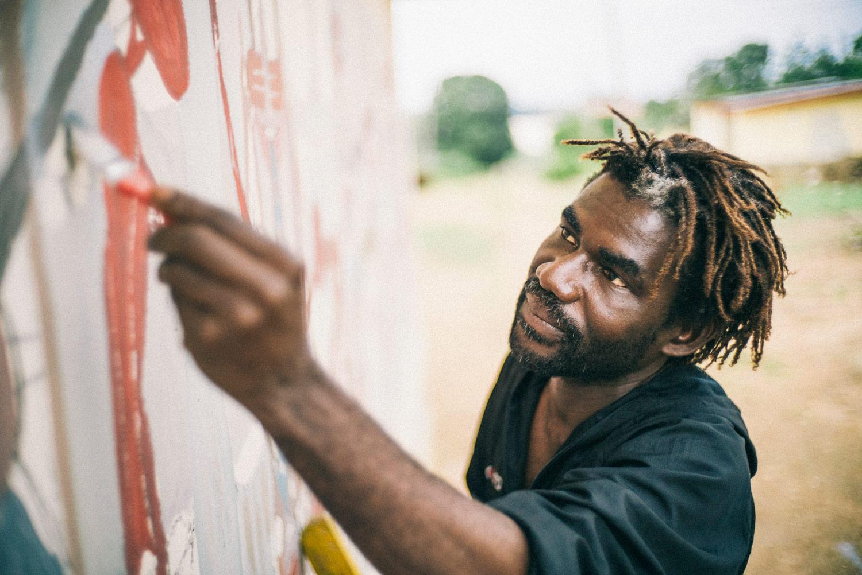 Akinjide Baruwa working on a mural in Ile-Ife in summer 2016. ©Silke Lapina