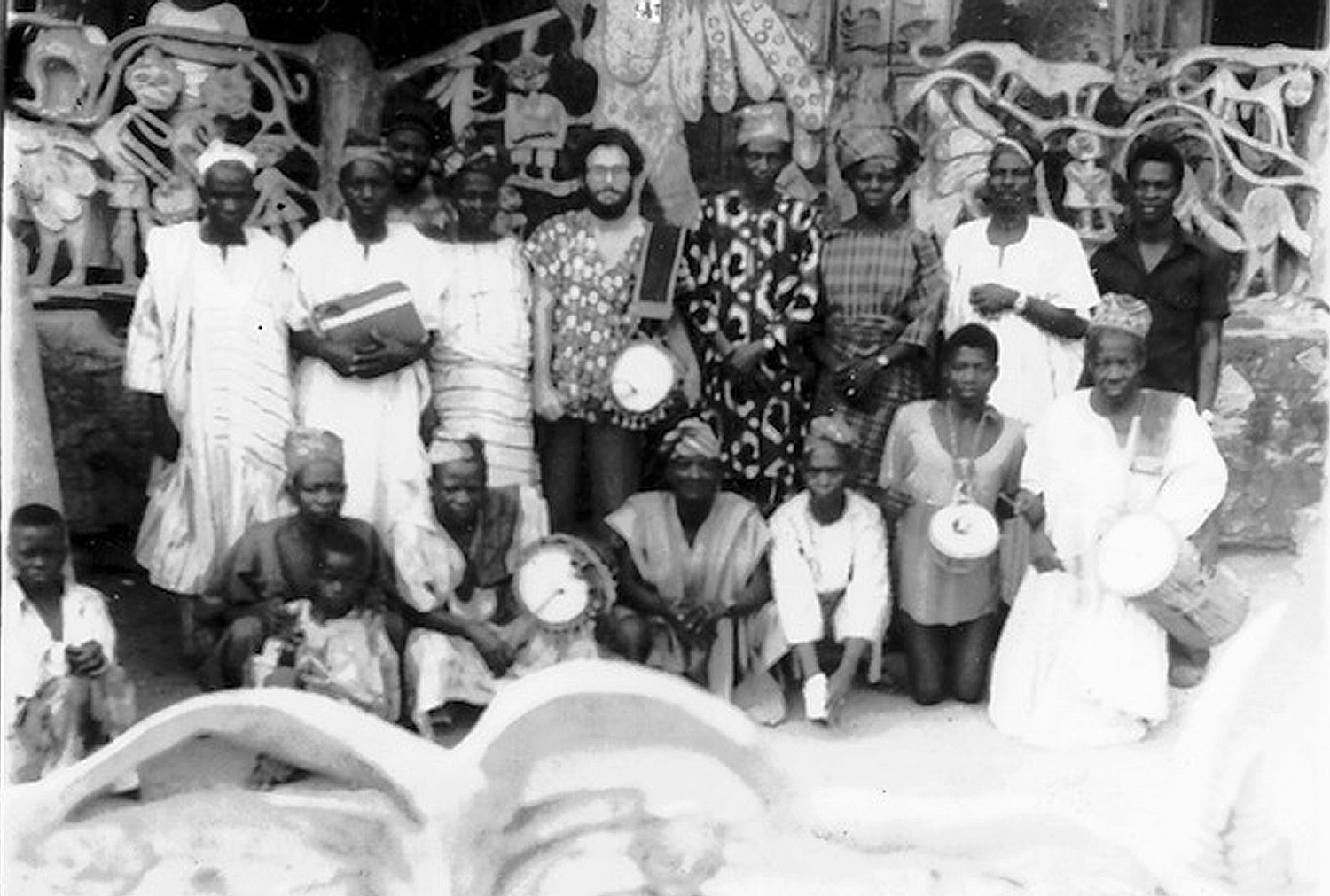 The Ritual Orchestra for the weekly ọ̀sẹ̀-ceremony in front of the house of Adunni Olorisha Susanne Wenger,Ibokún Road, Òṣogbo,1977. With Victor Manfredi, dùndùn drummer Ayan Kolade, Adigun Olosun, famous dancer Sango Sodo with his wife, who is one of the oriki singers, Iya Ikirun and Ayan Sipe, famous bàtá drummer.©Victor Manfredi
