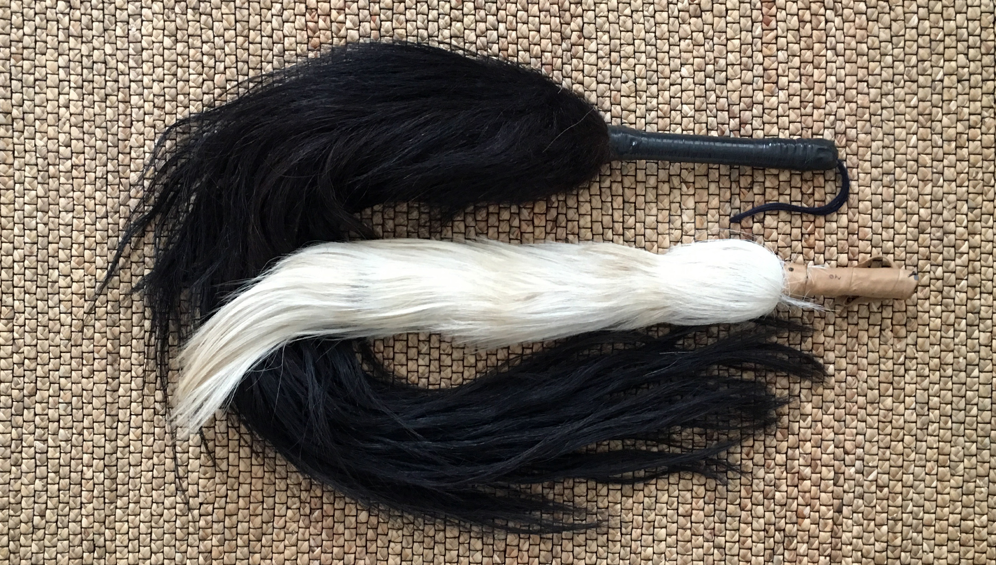 "Two different types of simple ""iruke"", Yorùbá royal regalia, made of horsetails.The black one is typical for Oya, the white one for Obatala. ©orishaimage.com"
