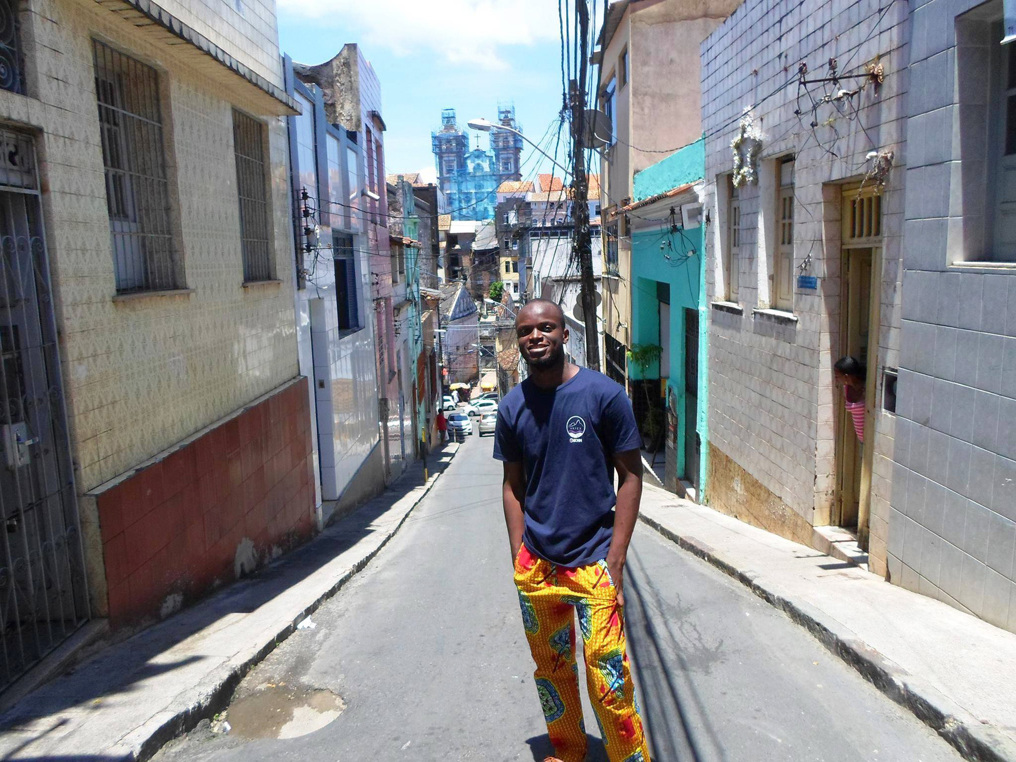 Yassin da Gloria from Benin in Salvador da Bahia, standing next to the building where his ancestor, Adriano Abubakar da Gloria was born in 1833. Adriano was born to freed Nagô parents, who still had one obligation: to serve their previous female owner –herself a Nagô freedwoman– until her death. ©Lisa Earl Castillo