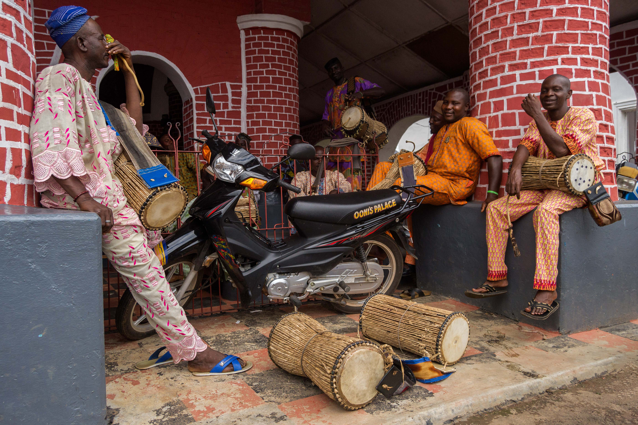 Dùndún-drummers at the Ọọ̀ni's palace in Ilé-Ifẹ̀. This tension drum mimicks the three melodic tones of the Yorùbá language and thus is called a 'talking drum', like the bàtá drum that is also known in the Cuban Yorùbá diaspora. Photo  Wikimedia Commons / Dotun55 / CC BY-SA 4.0