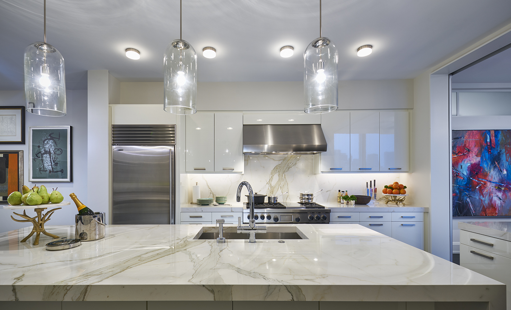 Three custom glass light fixtures from New Metal Crafts wash the island in light.