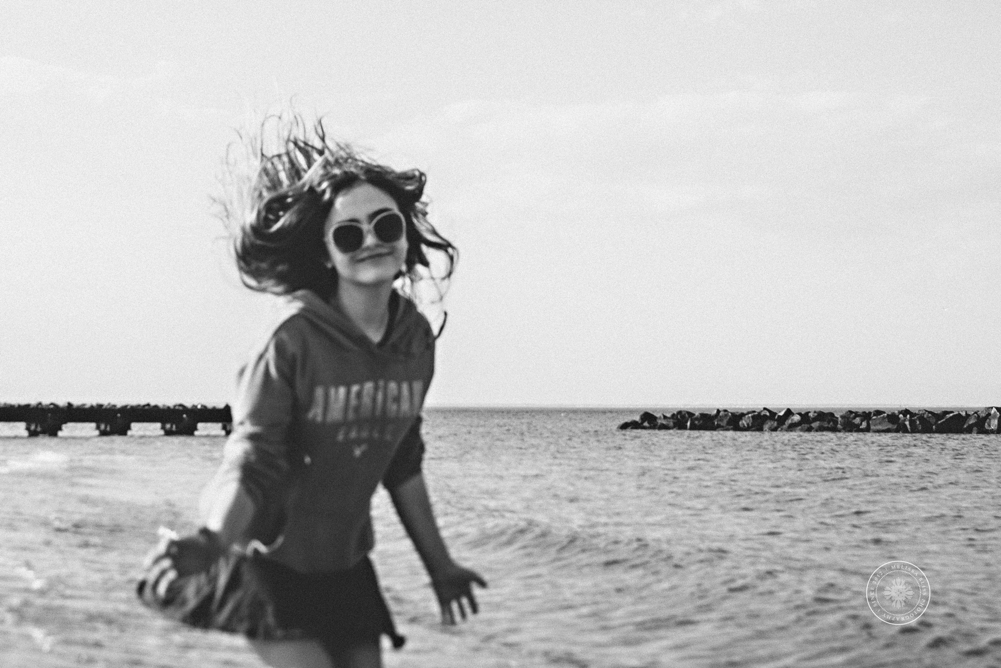 melissa-bliss-photography-fun-candid-beach-photos-teen-in-sunglasses-black-and-white