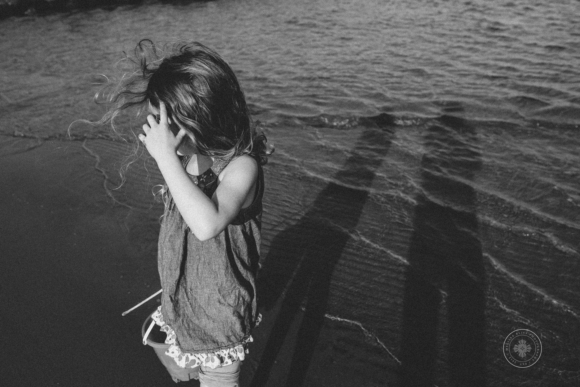 sandbridge-photographers-melissa-bliss-photography-black-and-white-photo-young-girl-on-the-shore