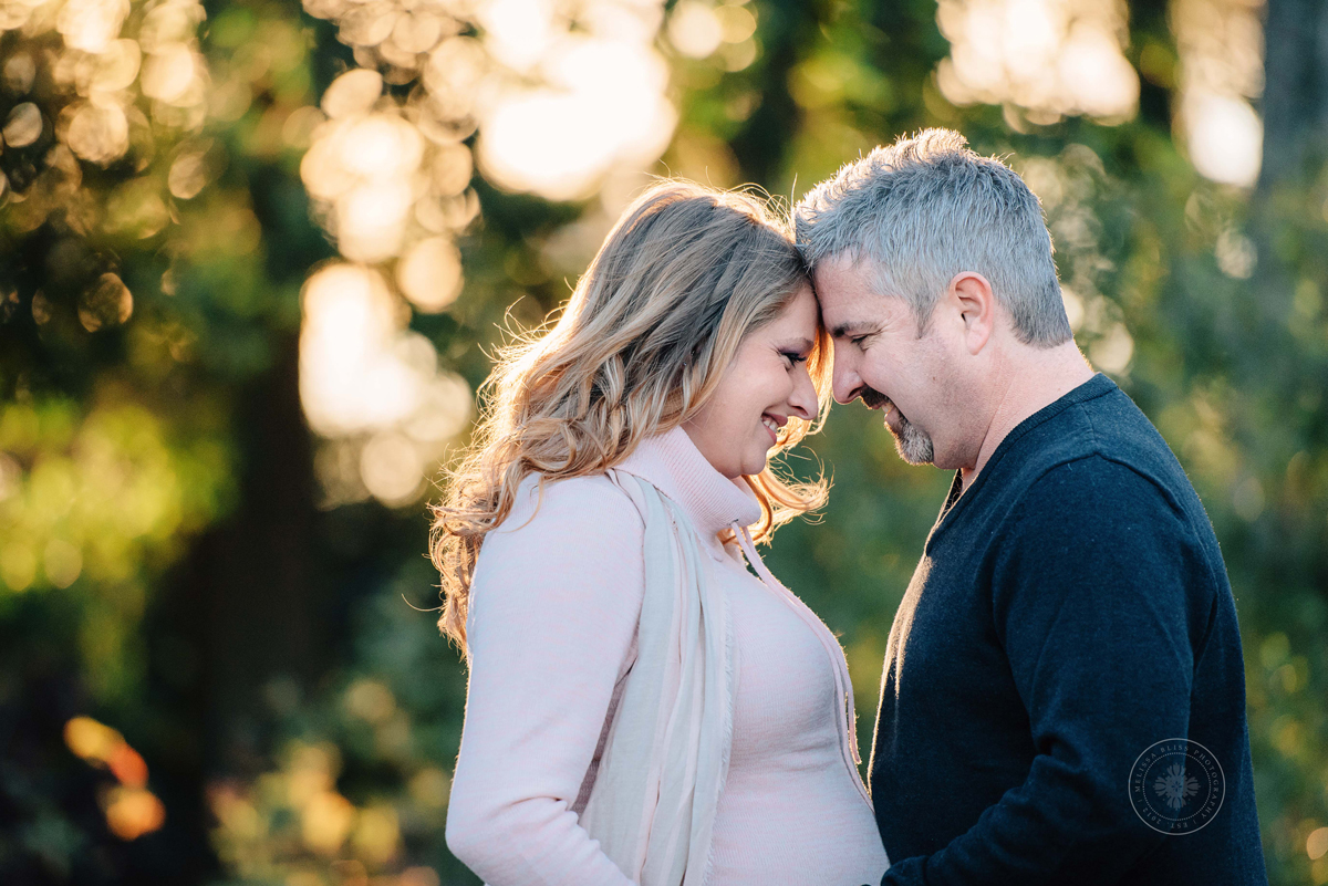 virginia-beach-norfolk-photographers-couple-embraces-at-maternity-session-the-hermitage-gardens