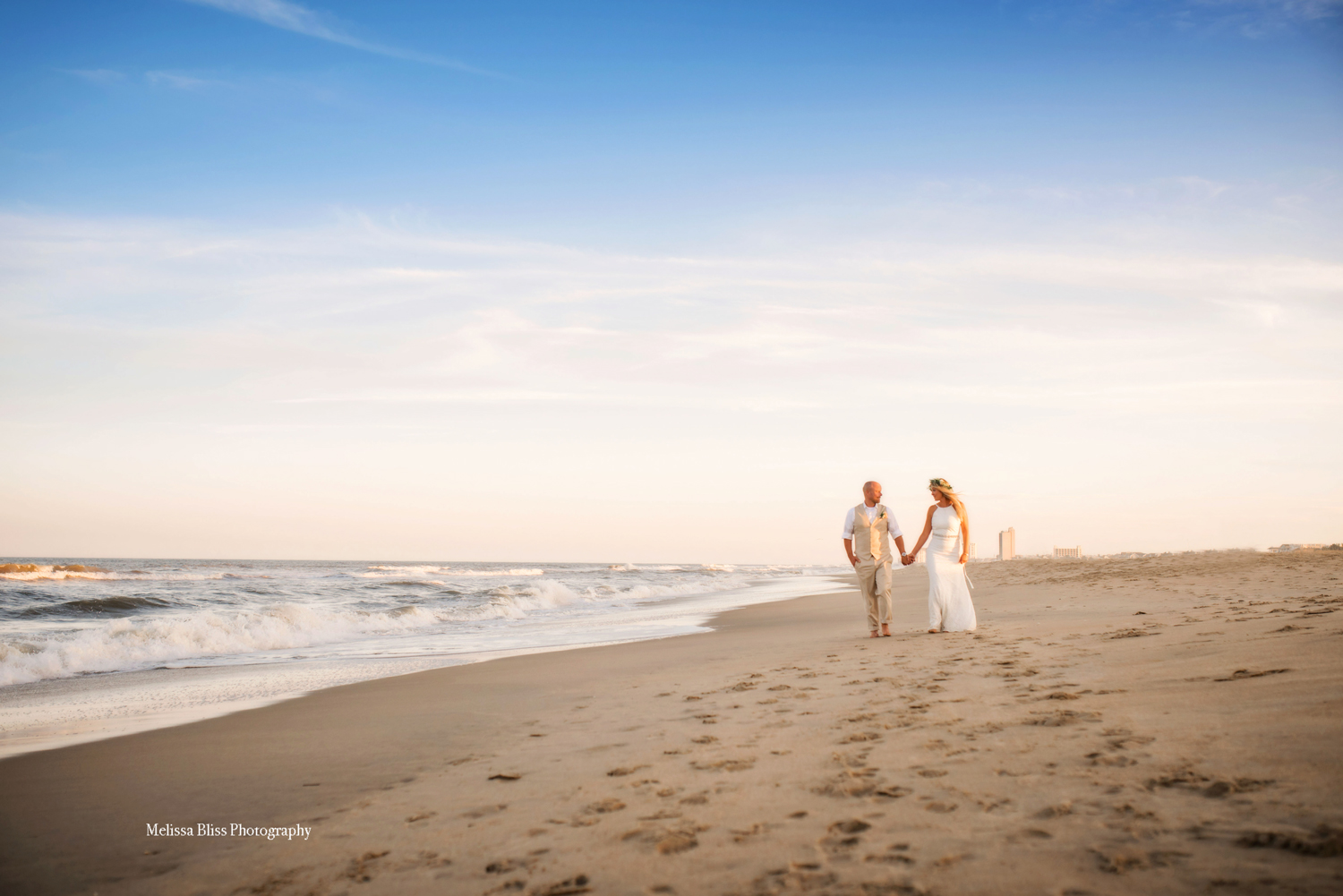 bride-and-groom-walk-along-shore-at-sunset-virginia-beach-oceanfront-intimate-wedding-by-melissa-bliss-photography-sandbridge-norfolk-va-beach-NC-wedding-photographer.jpg
